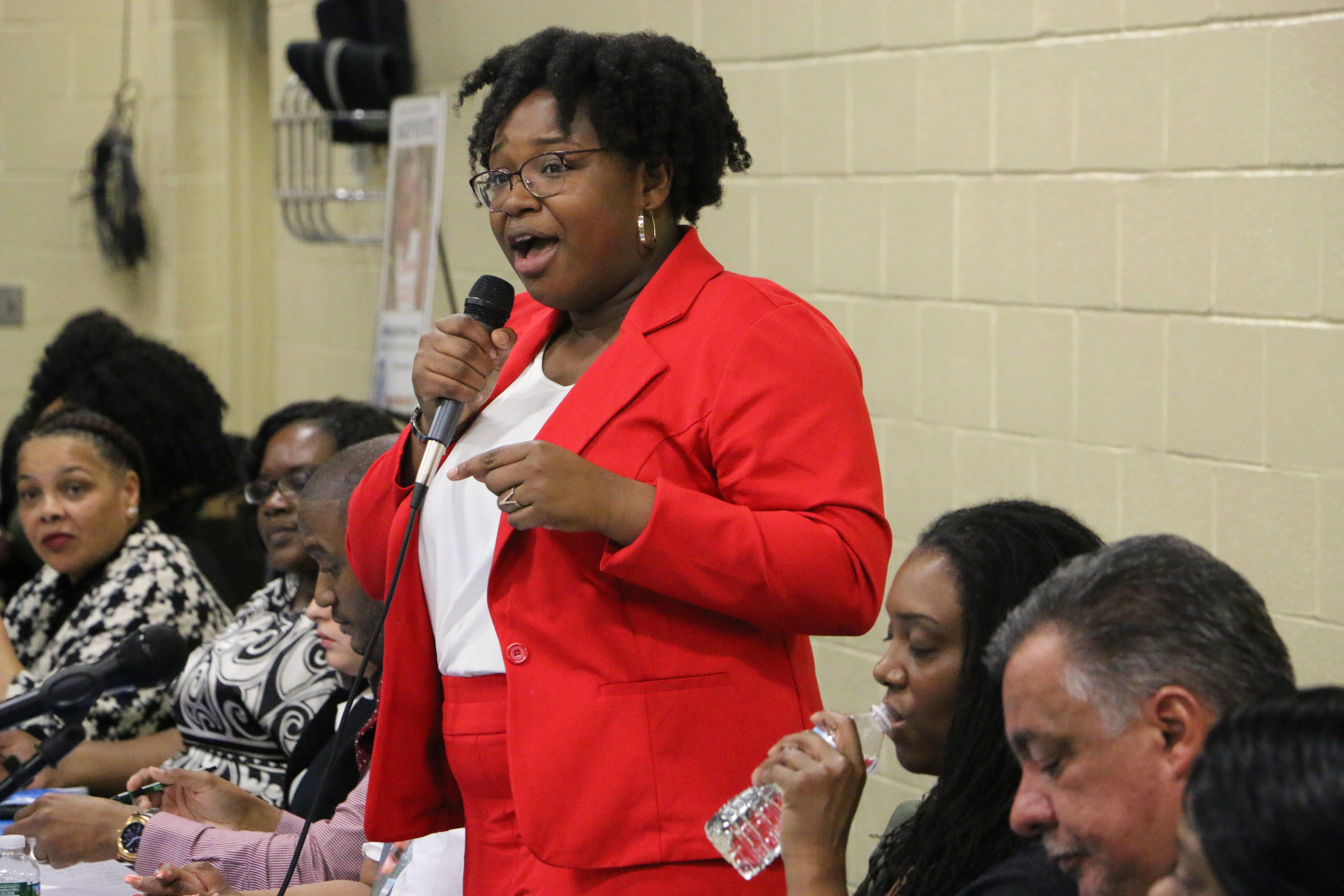 Newark Board of Education member A'Dorian Murray-Thomas. wearing a red suit, speaks while holding a microphone.