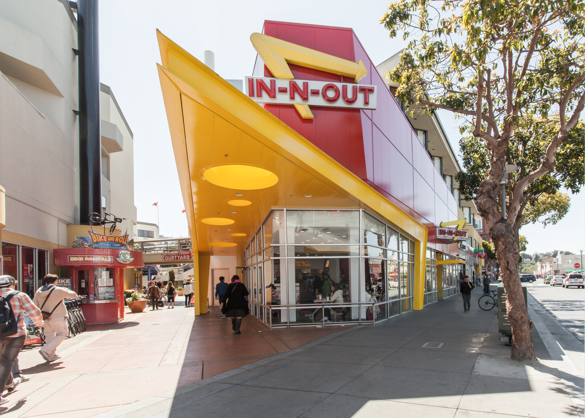 The front door of In-N-Out Burger at Fisherman's Wharf, including the restaurant's yellow, triangular awning and iconic yellow, red, and white sign.
