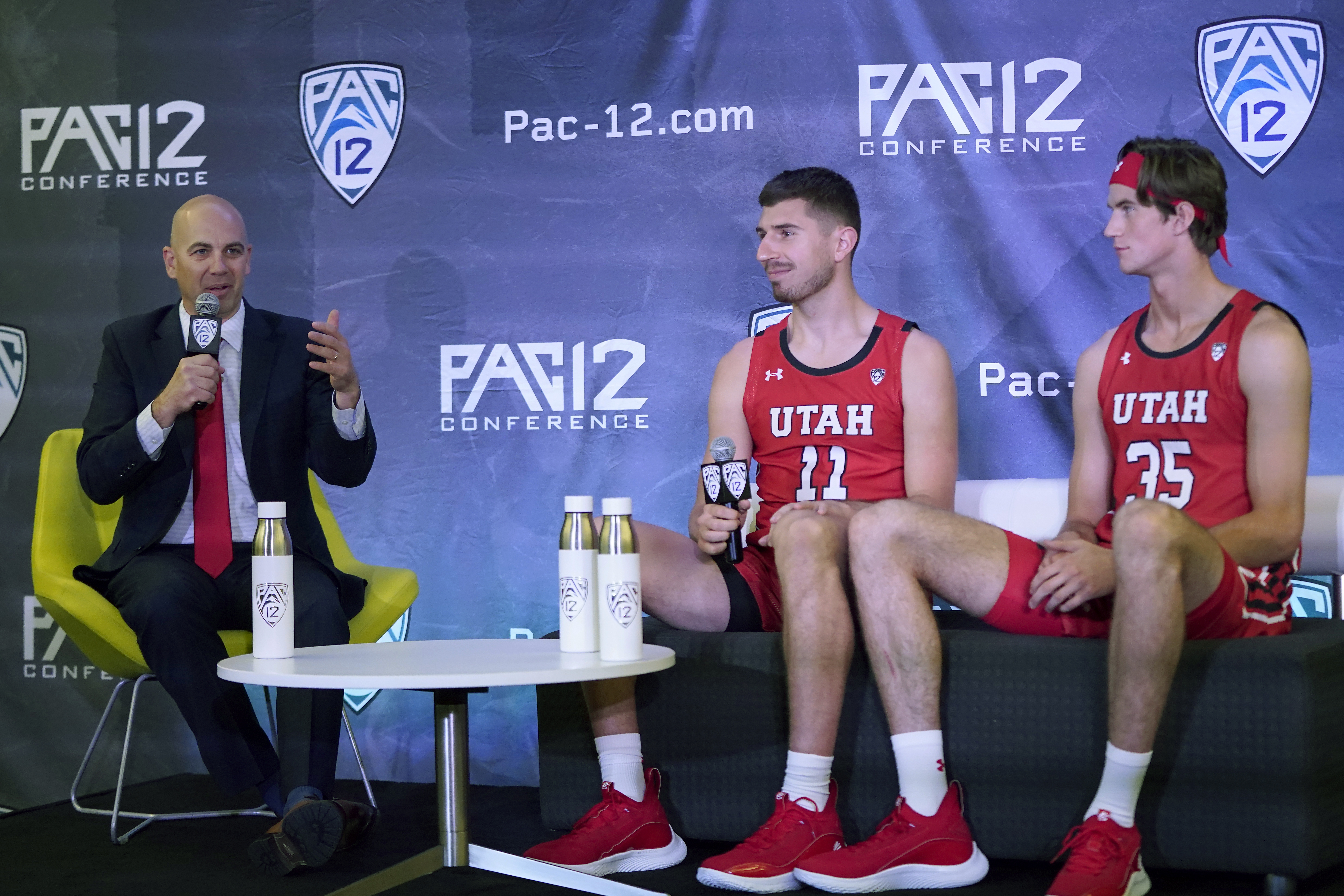 Utah coach Craig Smith, left, speaks next to Riley Battin, middle, and Branden Carlson during Pac-12 media day.