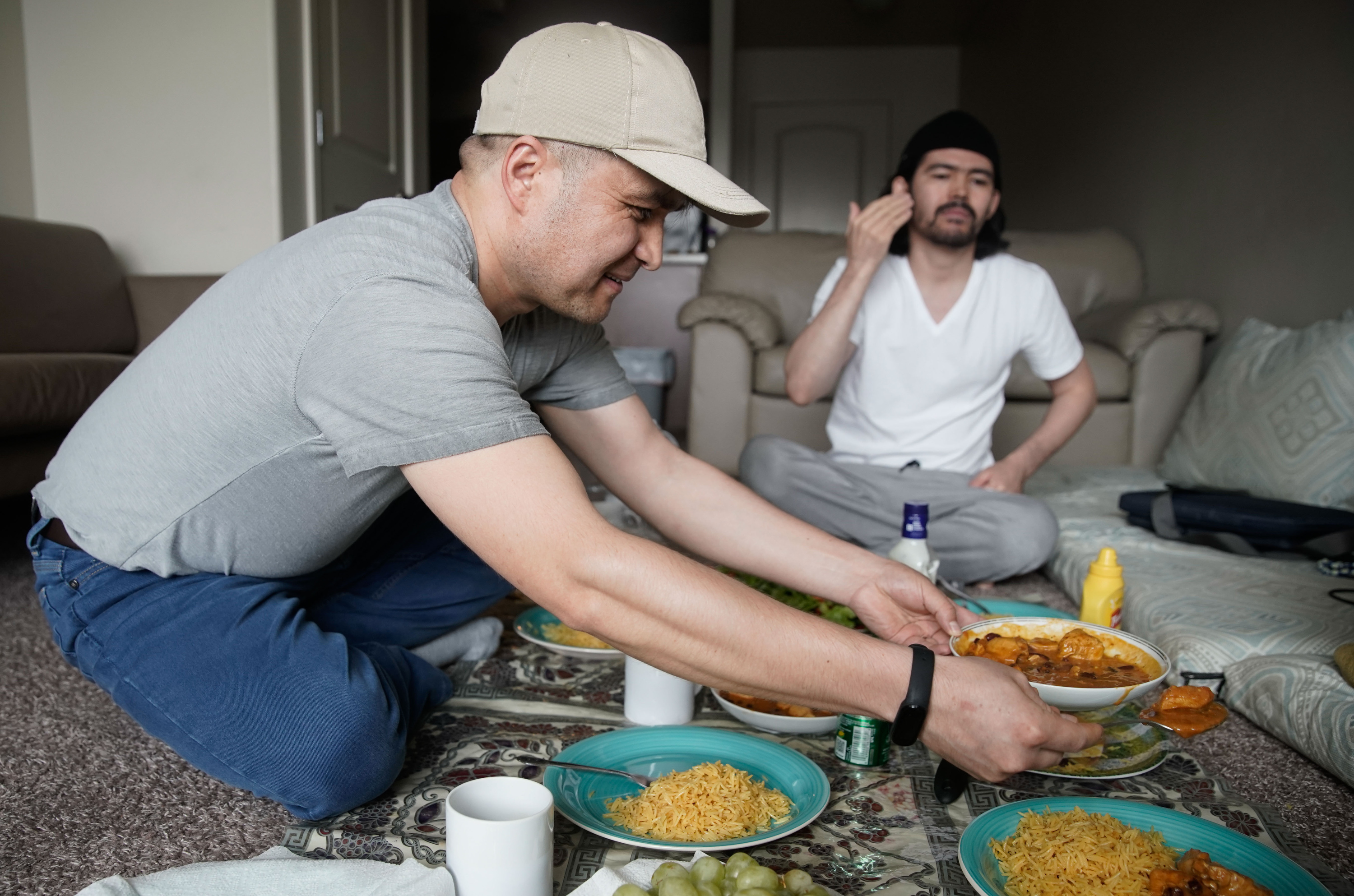 Azim Kakaie serves lunch to his flatmate, Hussain Yaqobi, in the living room of their home in Salt Lake City.