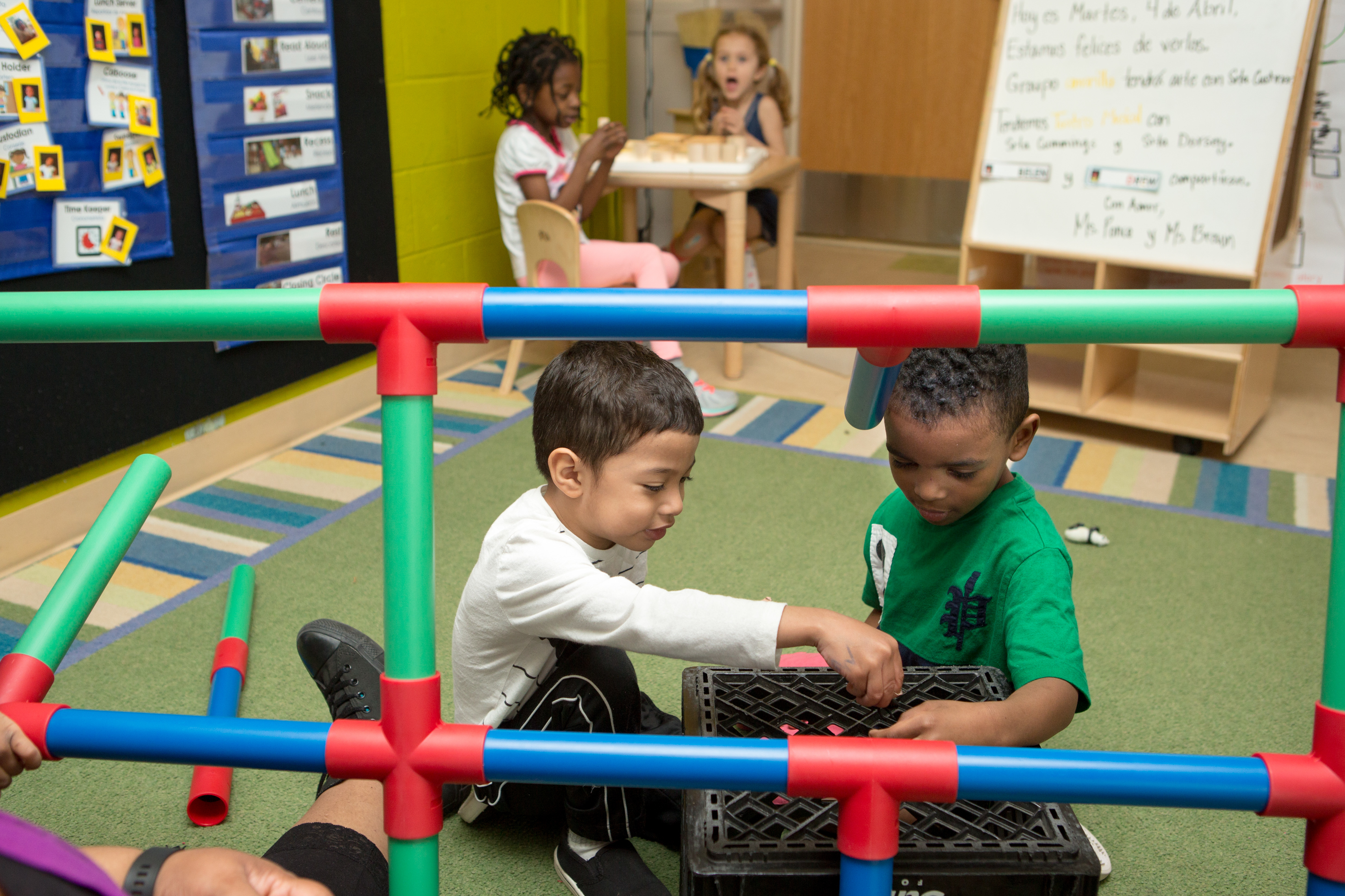 Two preschool boys in the foreground play on a mat in a classroom as two preschool girls sit at a table playing in the background.