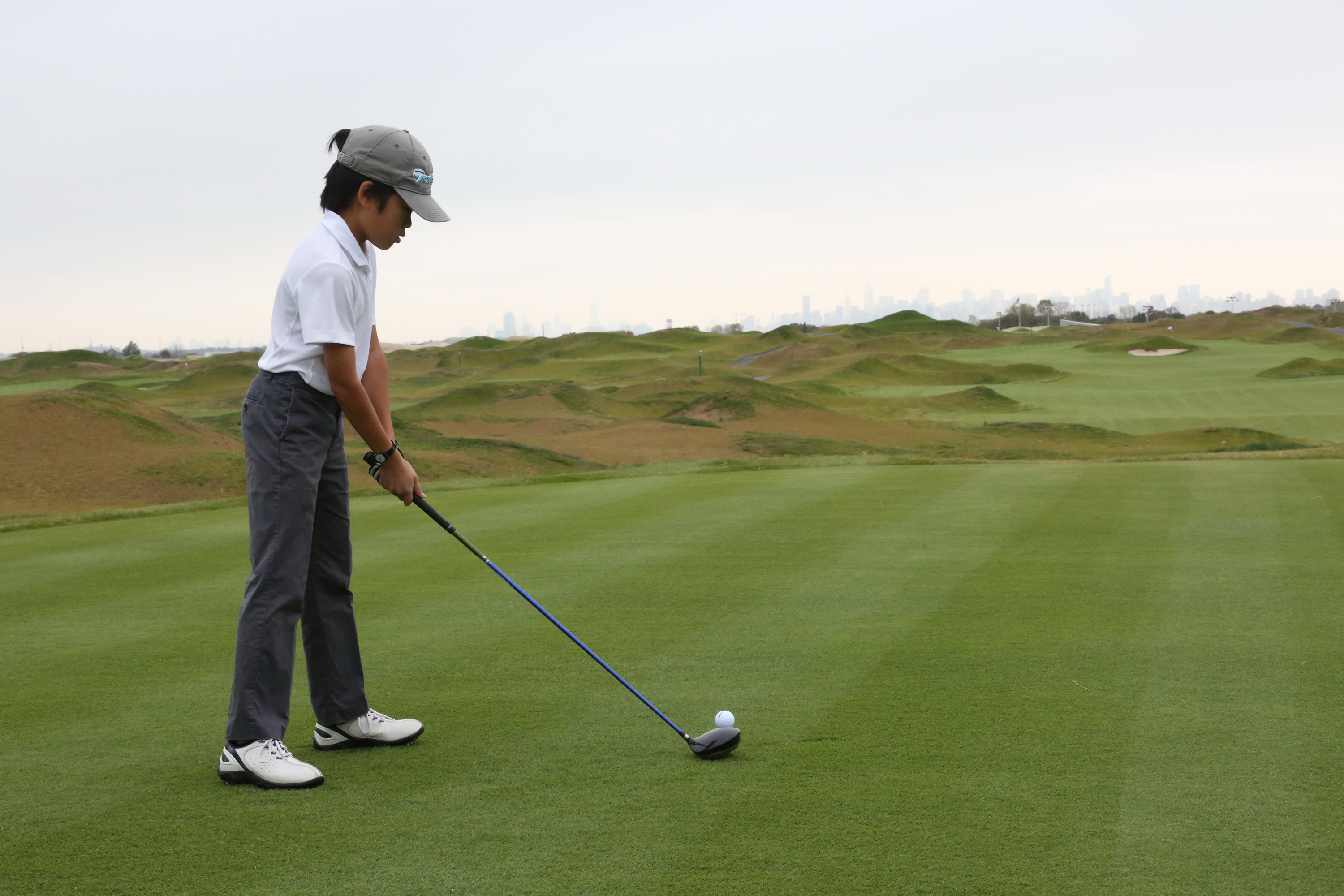A young player gets ready to tee off during the 2013 opening of the Trump Golf Links in The Bronx.