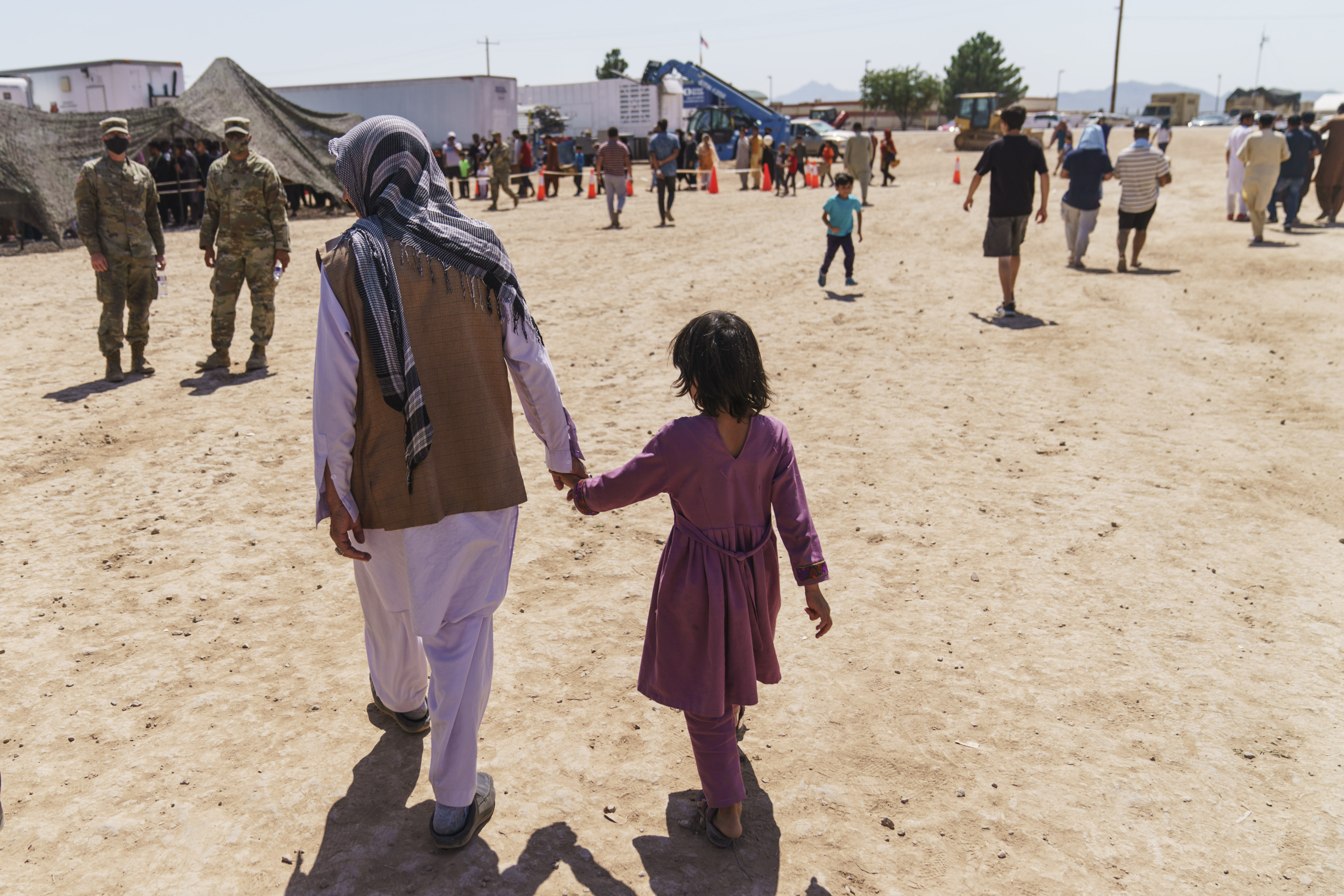A man walks with a child through Fort Bliss' Doña Ana Village where Afghan refugees are being housed, in New Mexico.