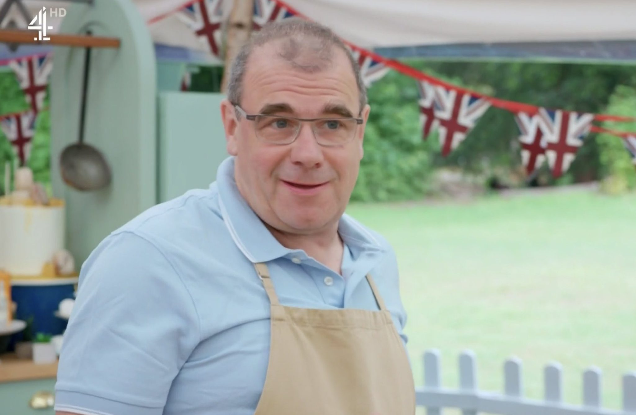 Jürgen in the Great British Bake Off tent, wearing a blue shirt and beige apron.