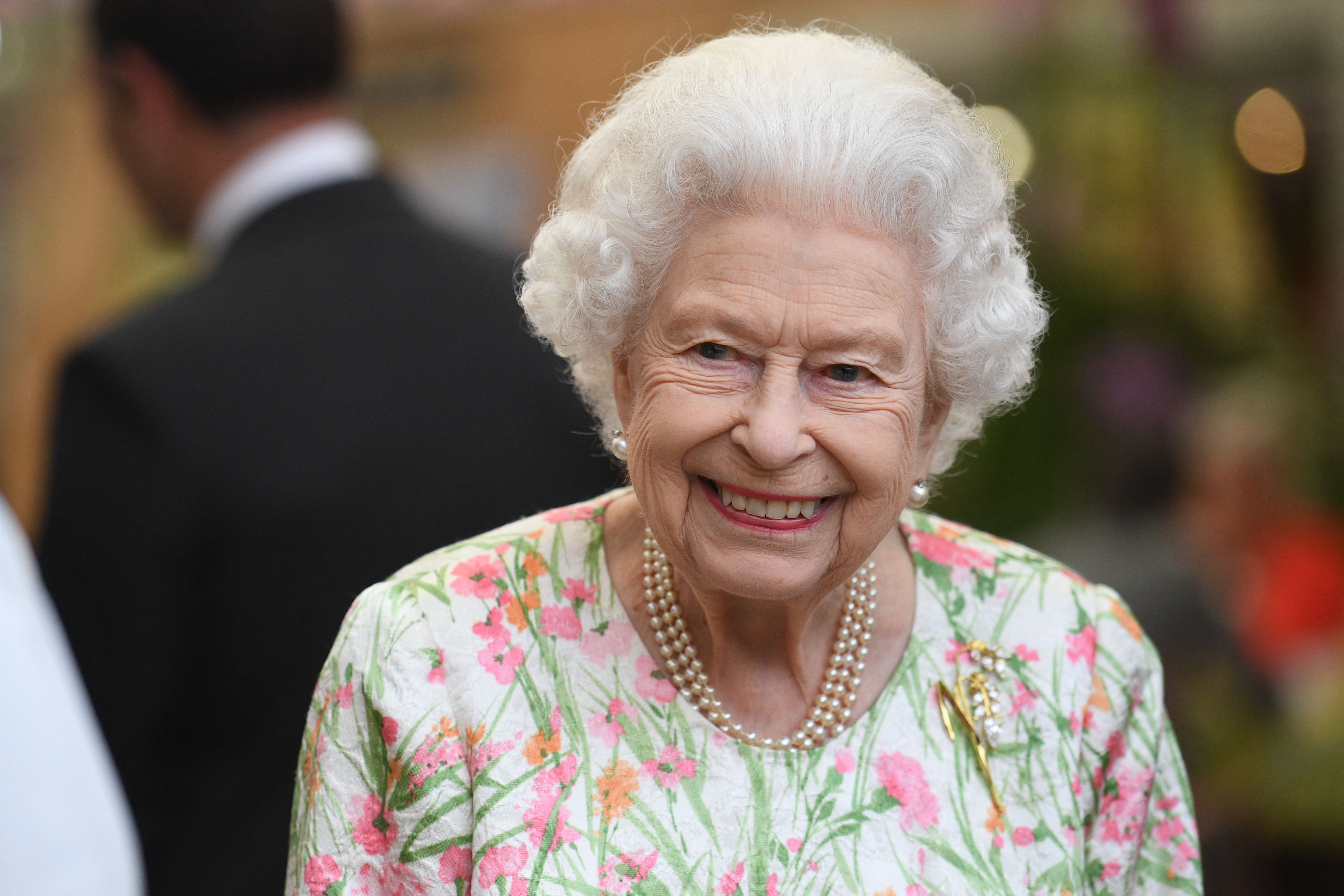 In this file photo taken on June 11, 2021, Britain's Queen Elizabeth II smiles as she attends an event in celebration of The Big Lunch initiative at The Eden Project, near St Austell in southwest England.