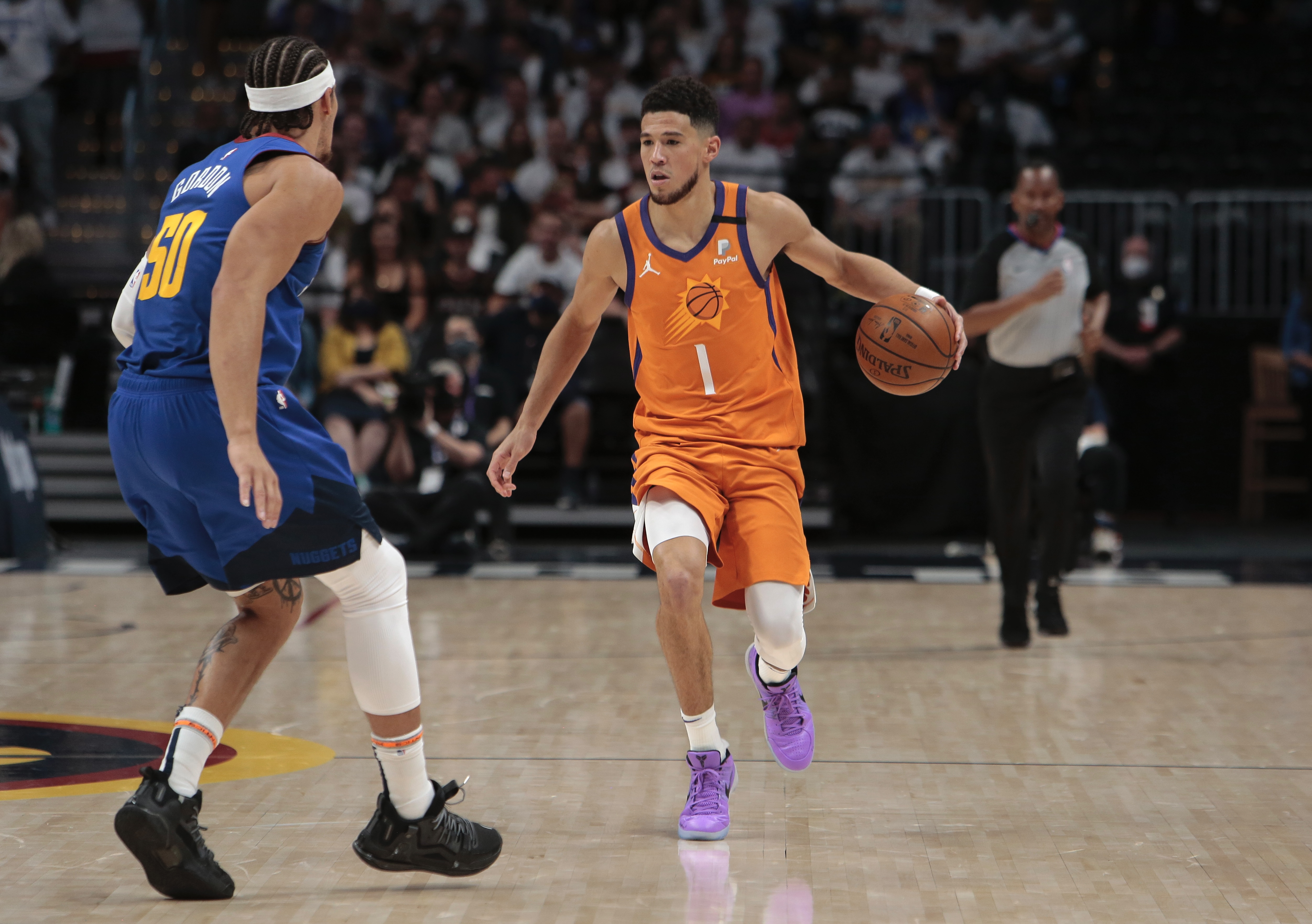 Devin Booker #1 of the Phoenix Suns dribbles the ball against the Denver Nuggets during Round 2, Game 3 of the 2021 NBA Playoffs on June 11, 2021 at the Ball Arena in Denver, Colorado.