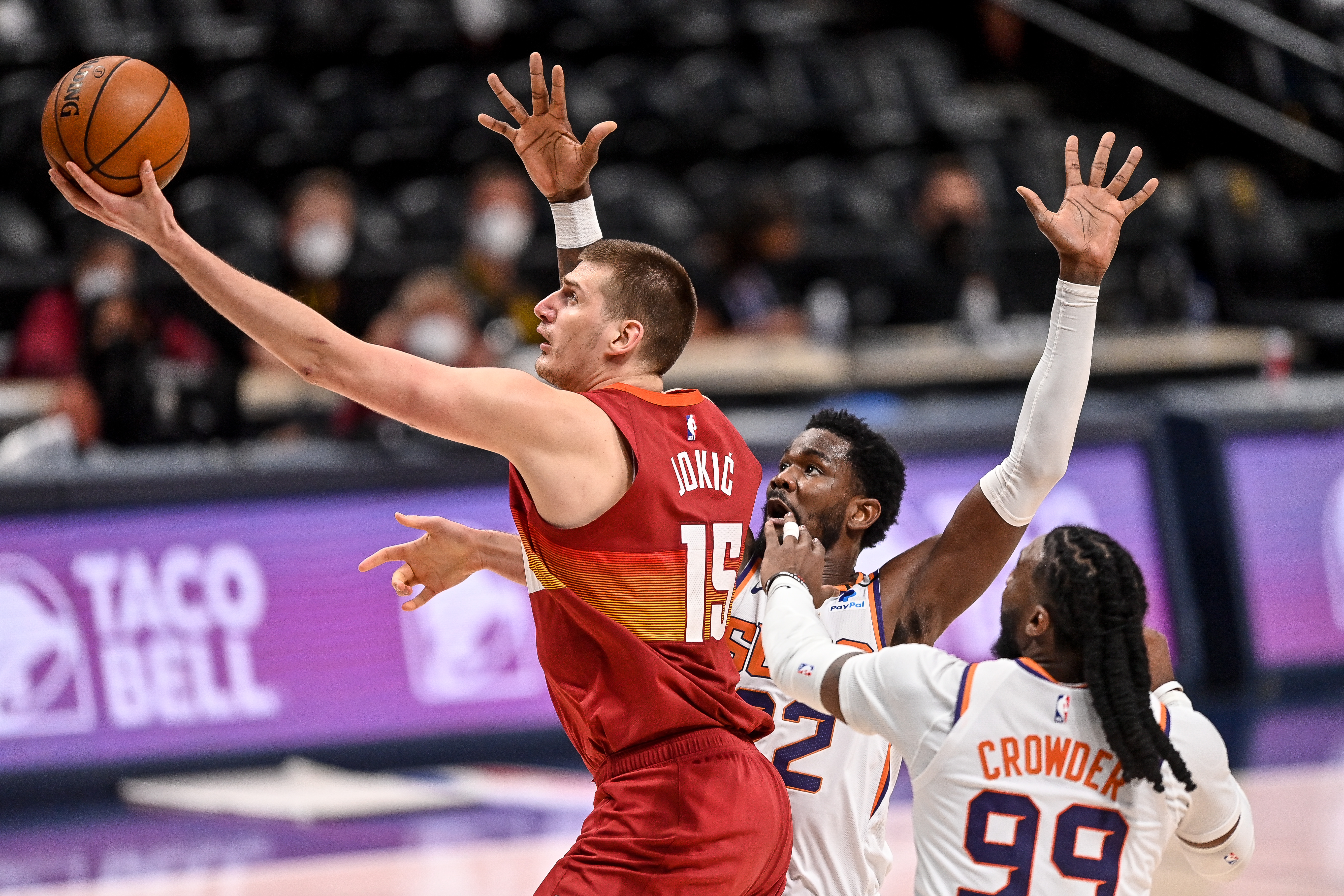 Nikola Jokic #15 of the Denver Nuggets scores on a layup past Jae Crowder #99 and Deandre Ayton #22 of the Phoenix Suns in Game Four of the Western Conference second-round playoff series at Ball Arena on June 13, 2021 in Denver, Colorado.
