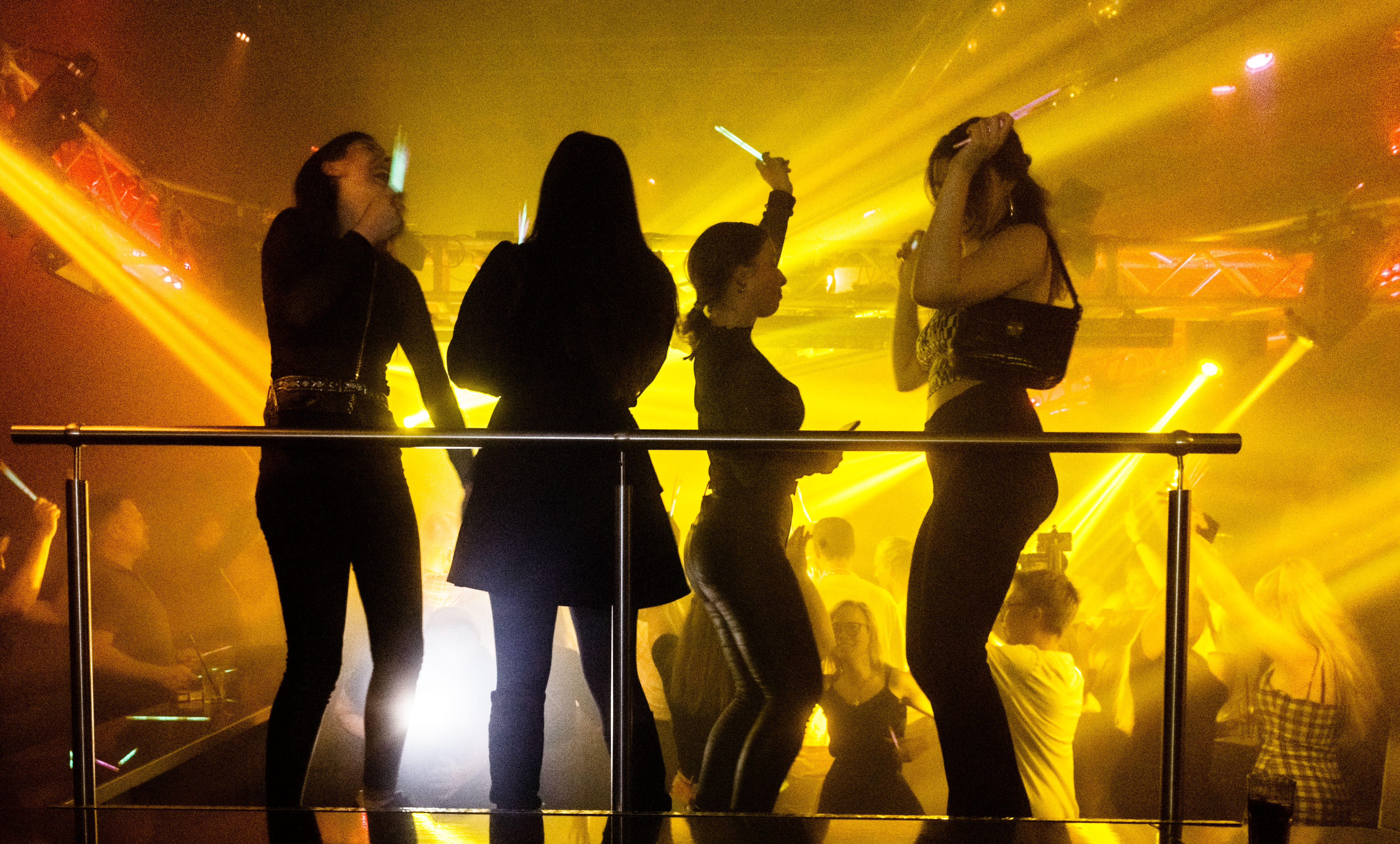 Four people dancing in a club and waving glow sticks.