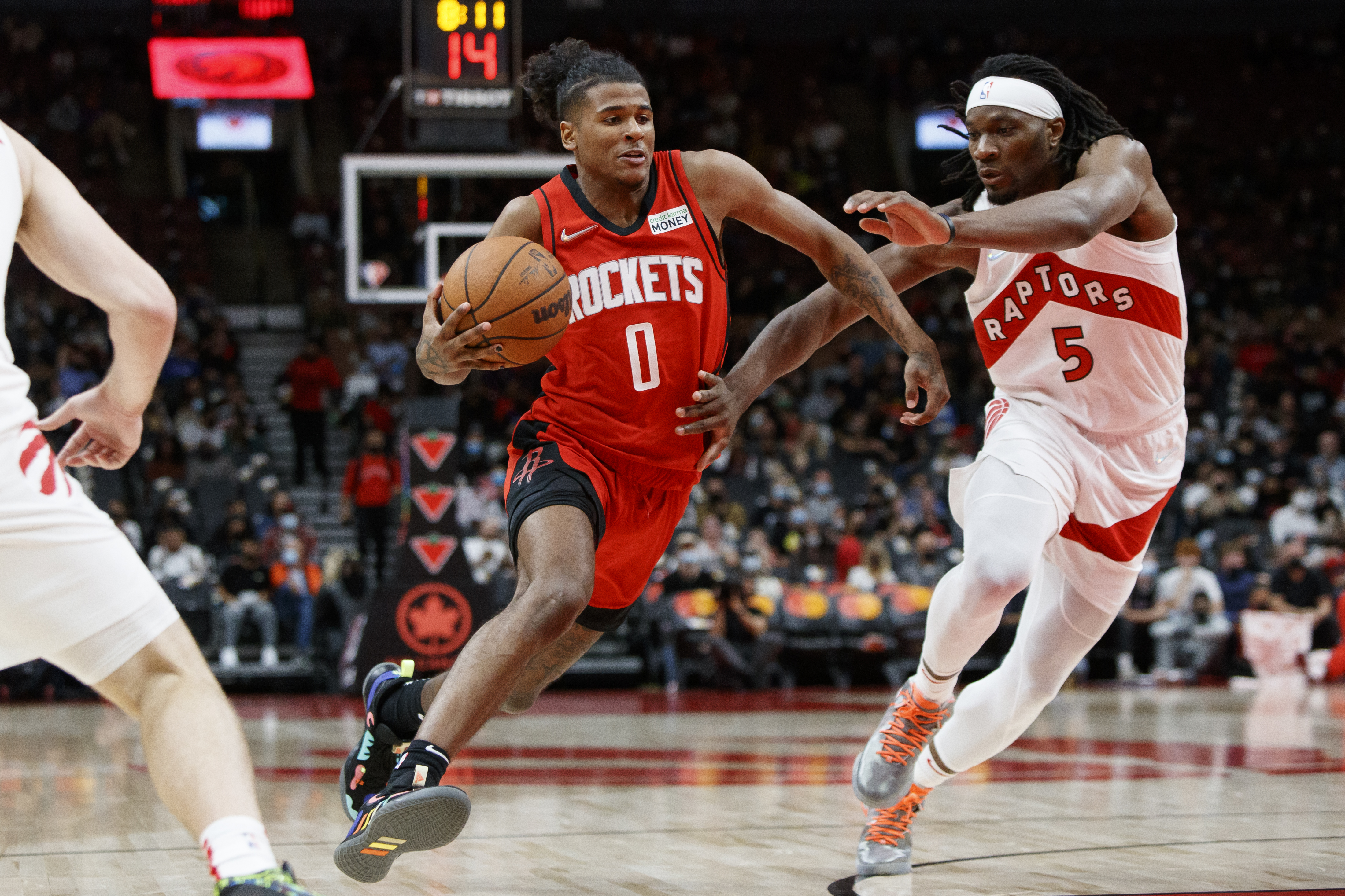 Jalen Green #0 of the Houston Rockets drives to the net on Precious Achiuwa #5 of the Toronto Raptors during pre-season NBA game action at Scotiabank Arena on October 11, 2021 in Toronto, Canada.