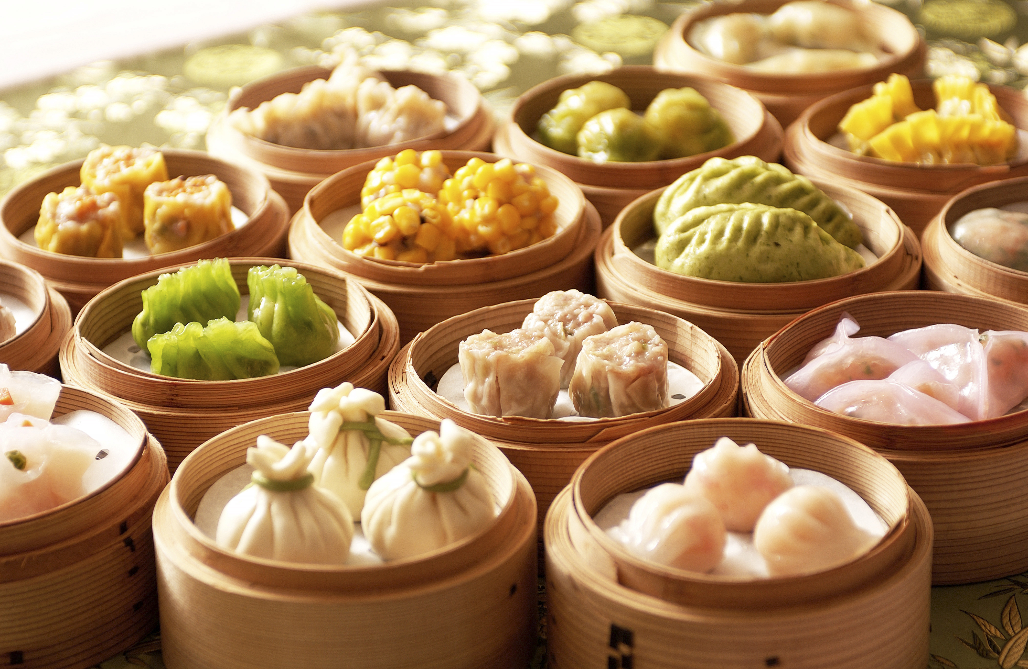 Pink, yellow, and green dumplings sit in steamers.