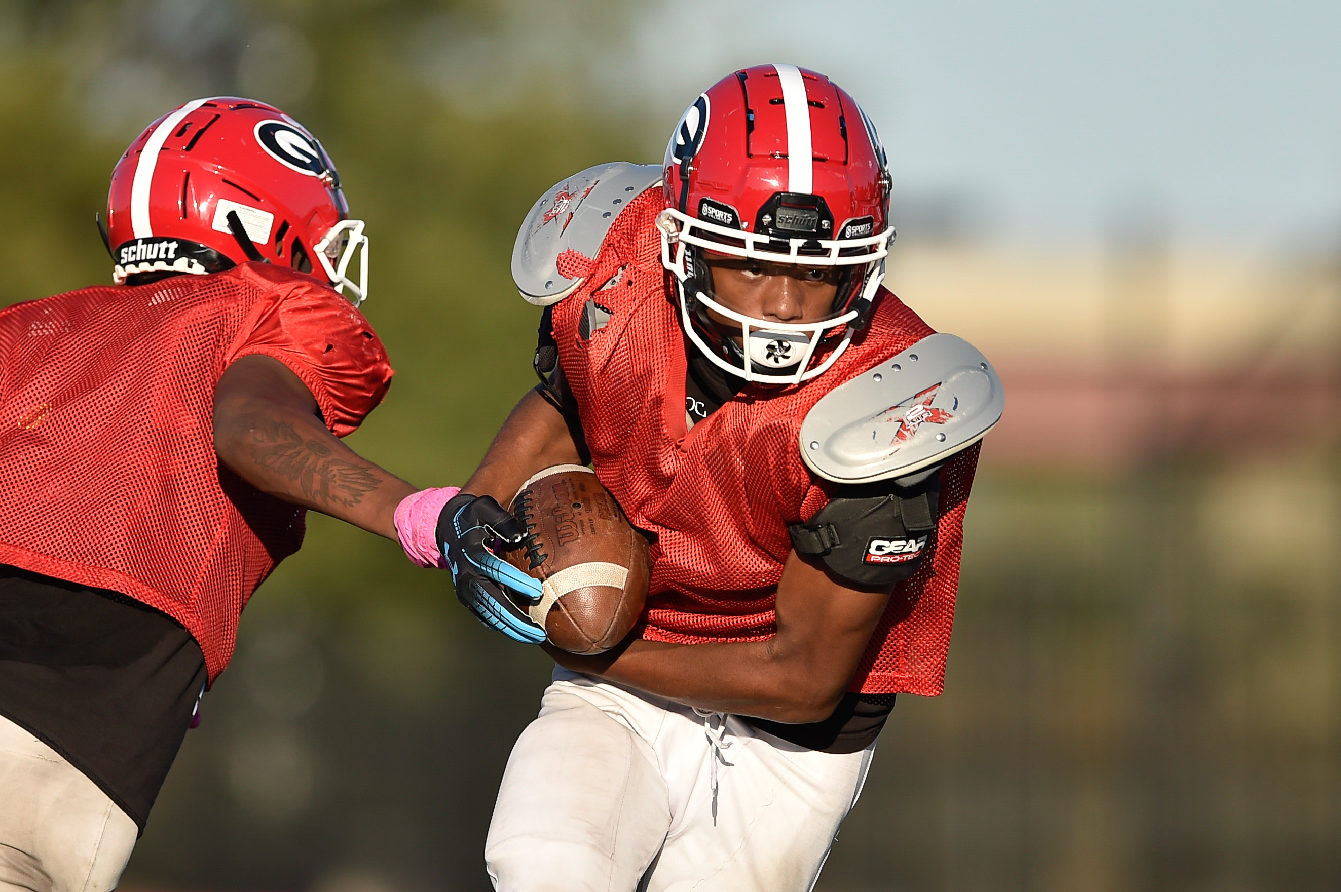 Goode's Martese Whitehurst takes the handoff from Marquis Brown during practice.