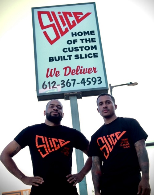 A photo of Slice's owners in front of their new signage.