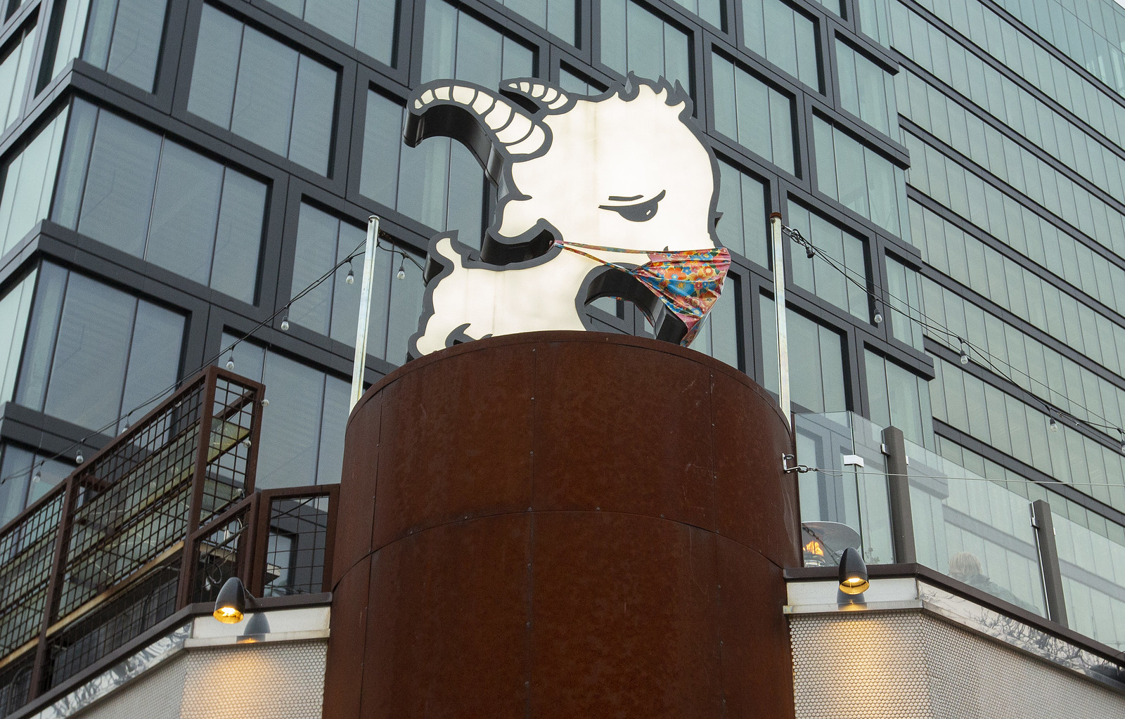 A cartoonish goat sign with a mask over it on the roof of a restaurant.