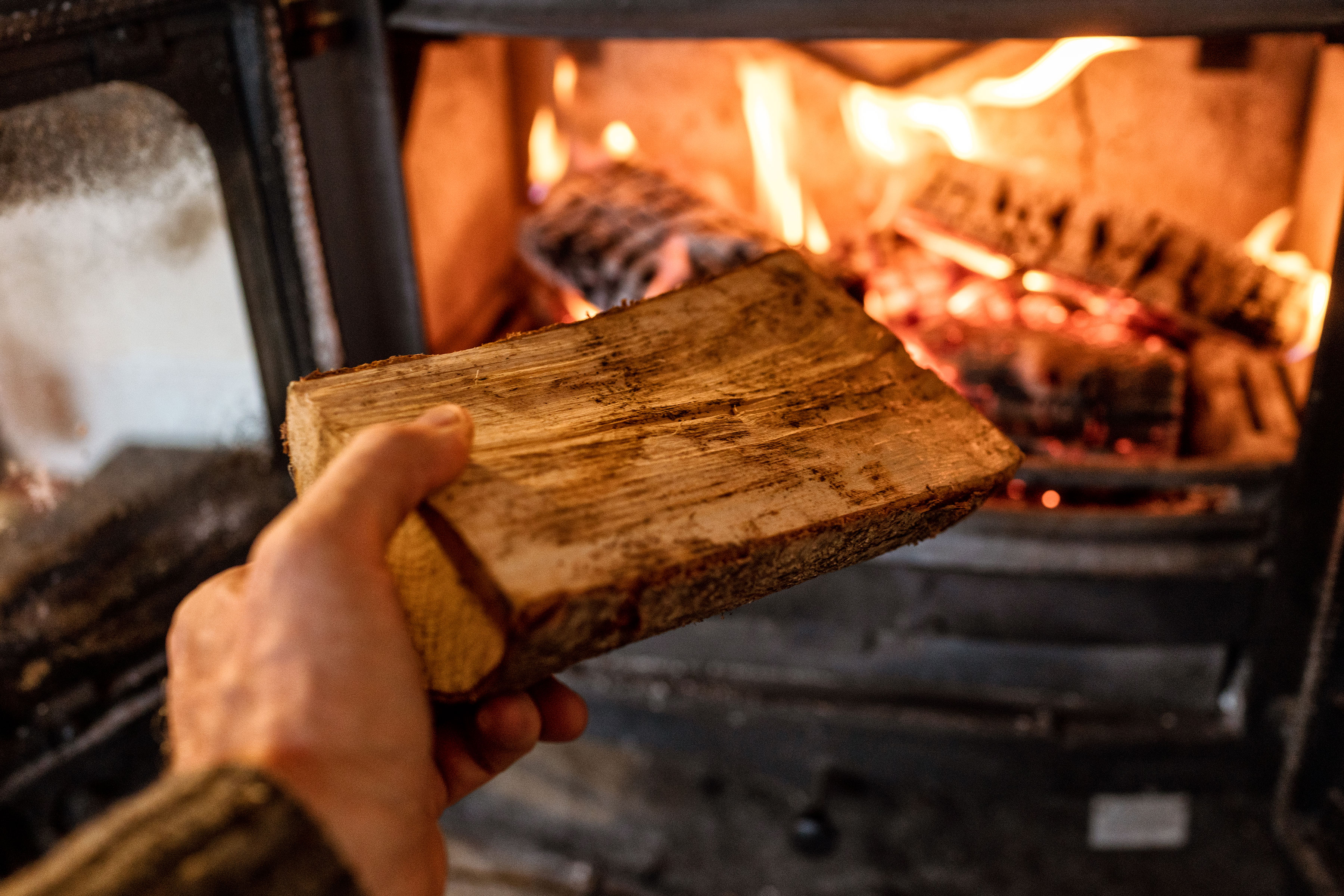 A hand placing a cut pice of wood into a lit wood burning stove.