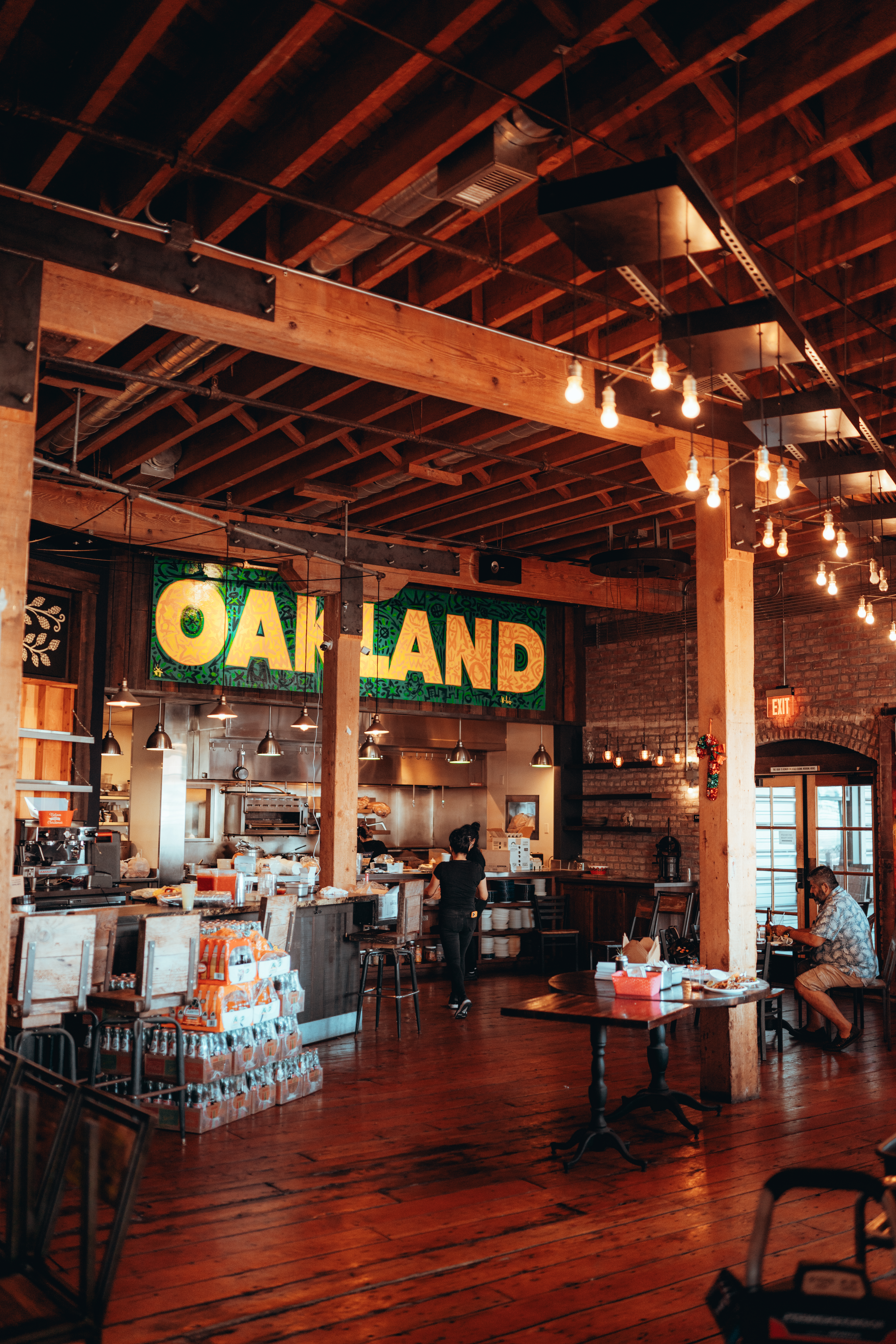 """A view of the front counter of La Santa Torta's brick-and-mortar restaurant, including a green-and-yellow sign reading """"Oakland."""""""