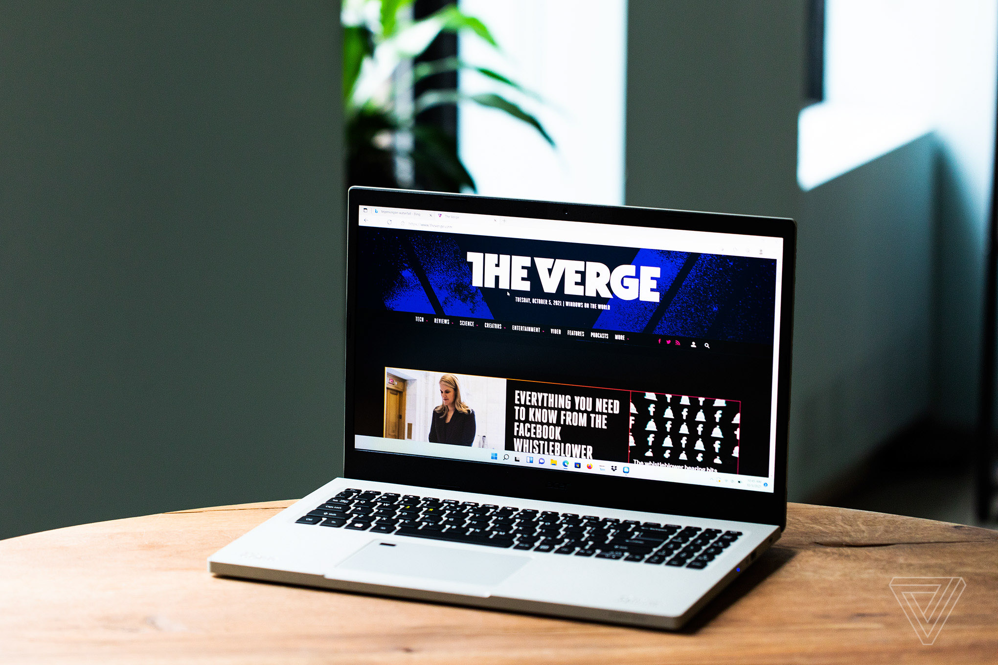 The Acer Aspire Vero open on a wooden table with a houseplant in the background. The screen displays The Verge homepage.