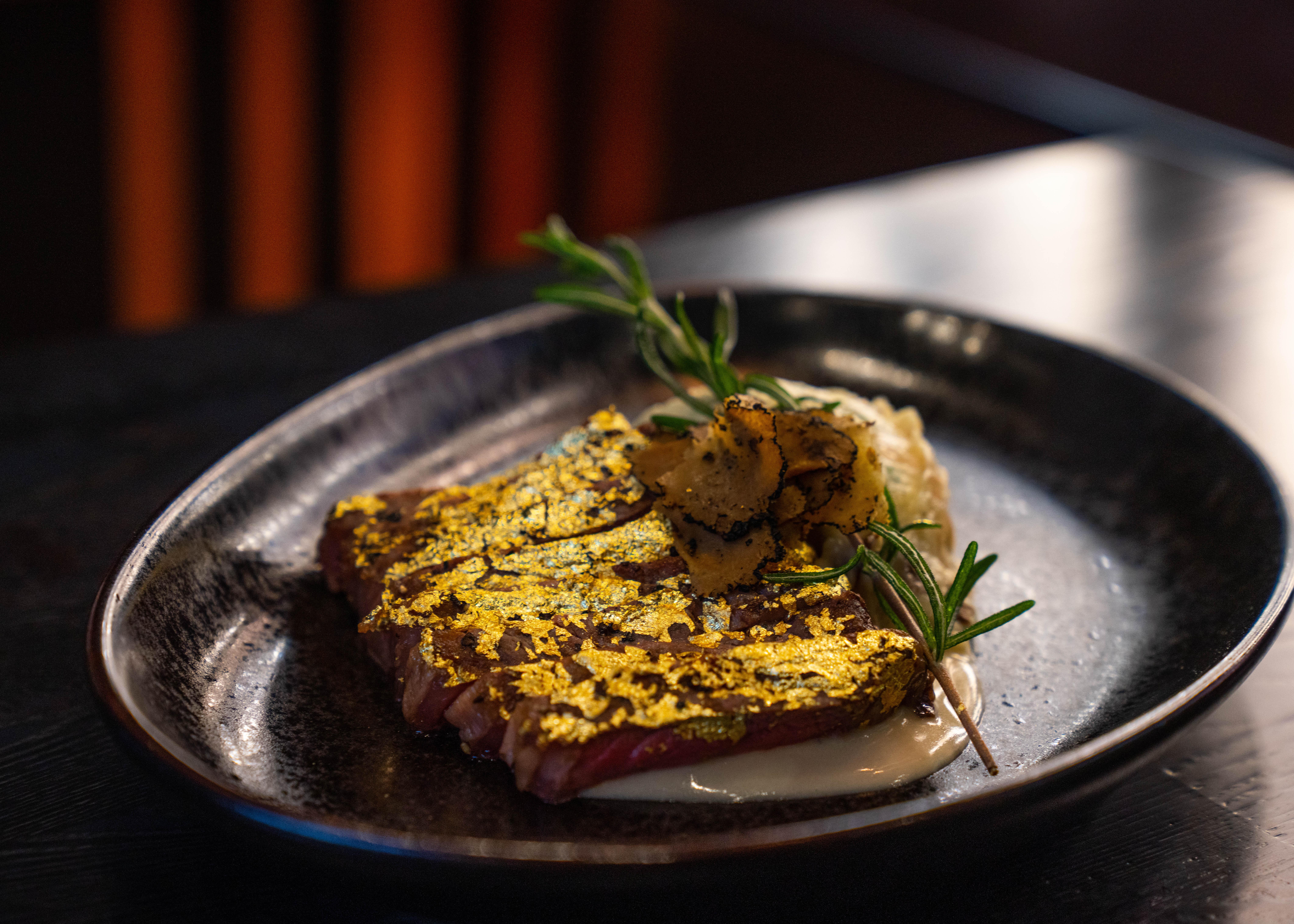 A strip steak covered in gold leaf at Mayflower Club.