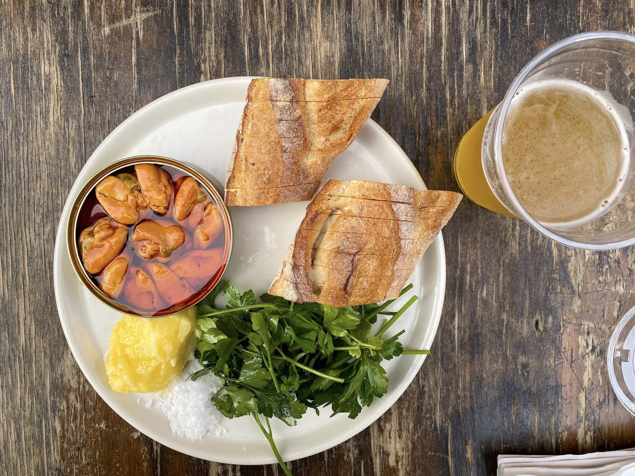 A plate with tinned fish served with a baguette, greens, salt, and butter with a cup of beer on the side.