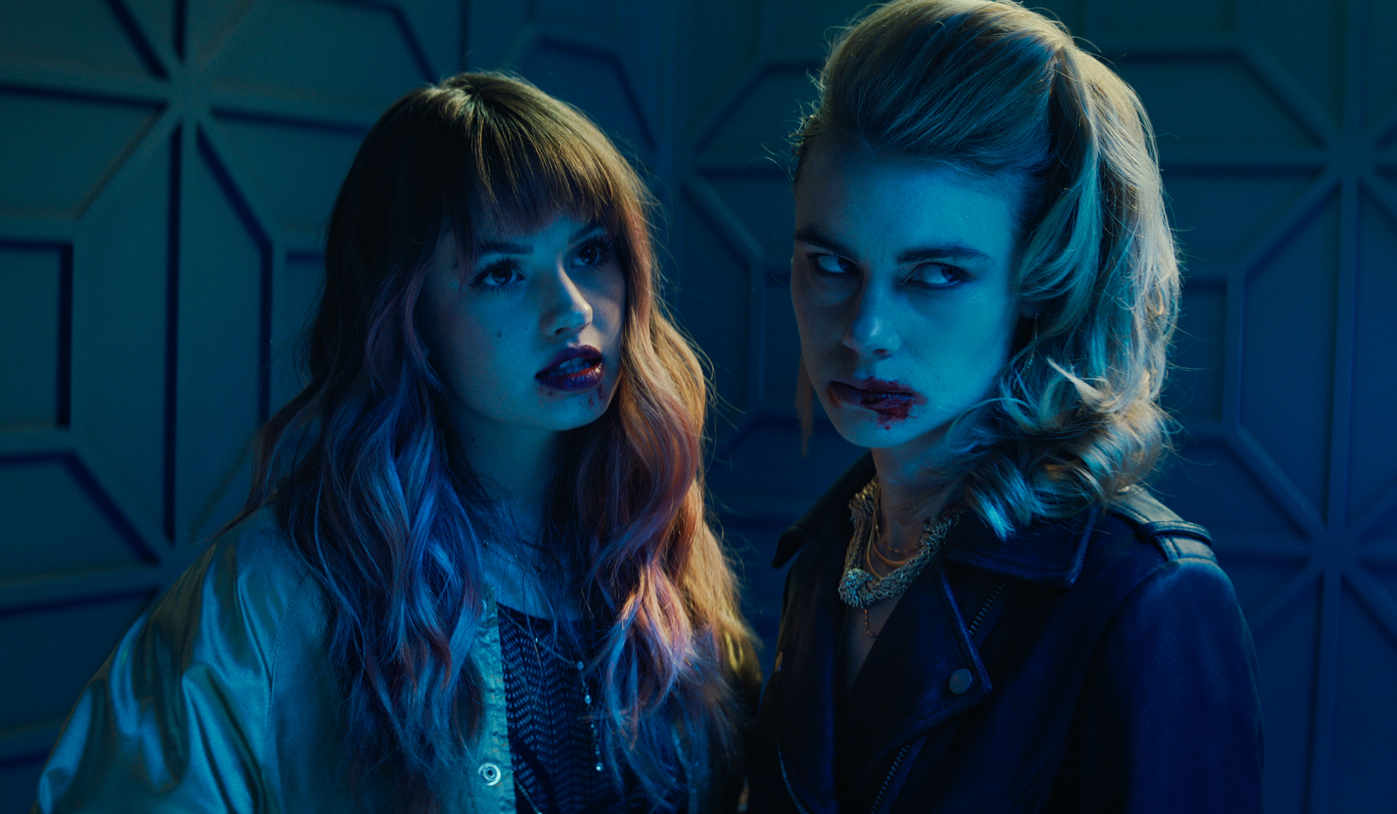 Two of Night Teeth's vampires, Blaire (Debby Ryan) and Zoe (Lucy Fry), stand together in a dimly lit room, with their mouths bloody