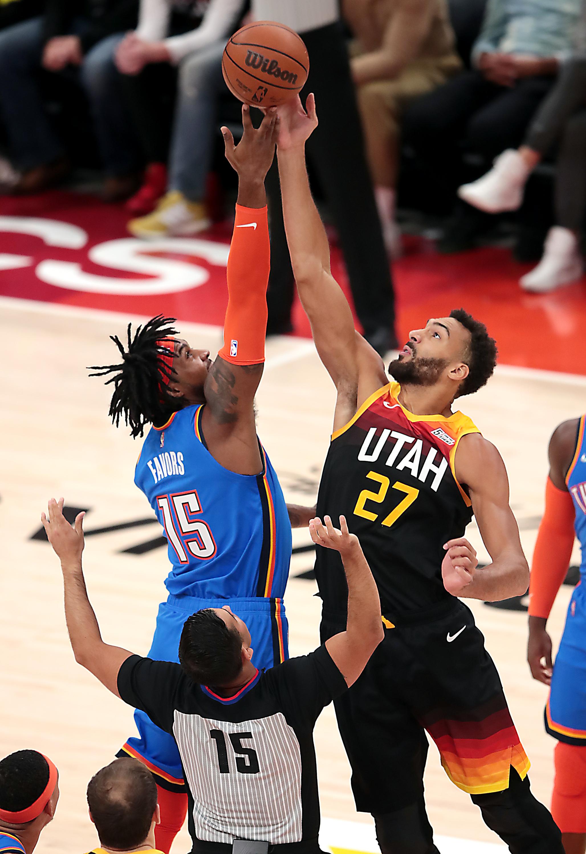 Oklahoma City Thunder center Derrick Favors, wearing a blue jersey, and Utah Jazz center Rudy Gobert, wearing a black jerssey, tip off