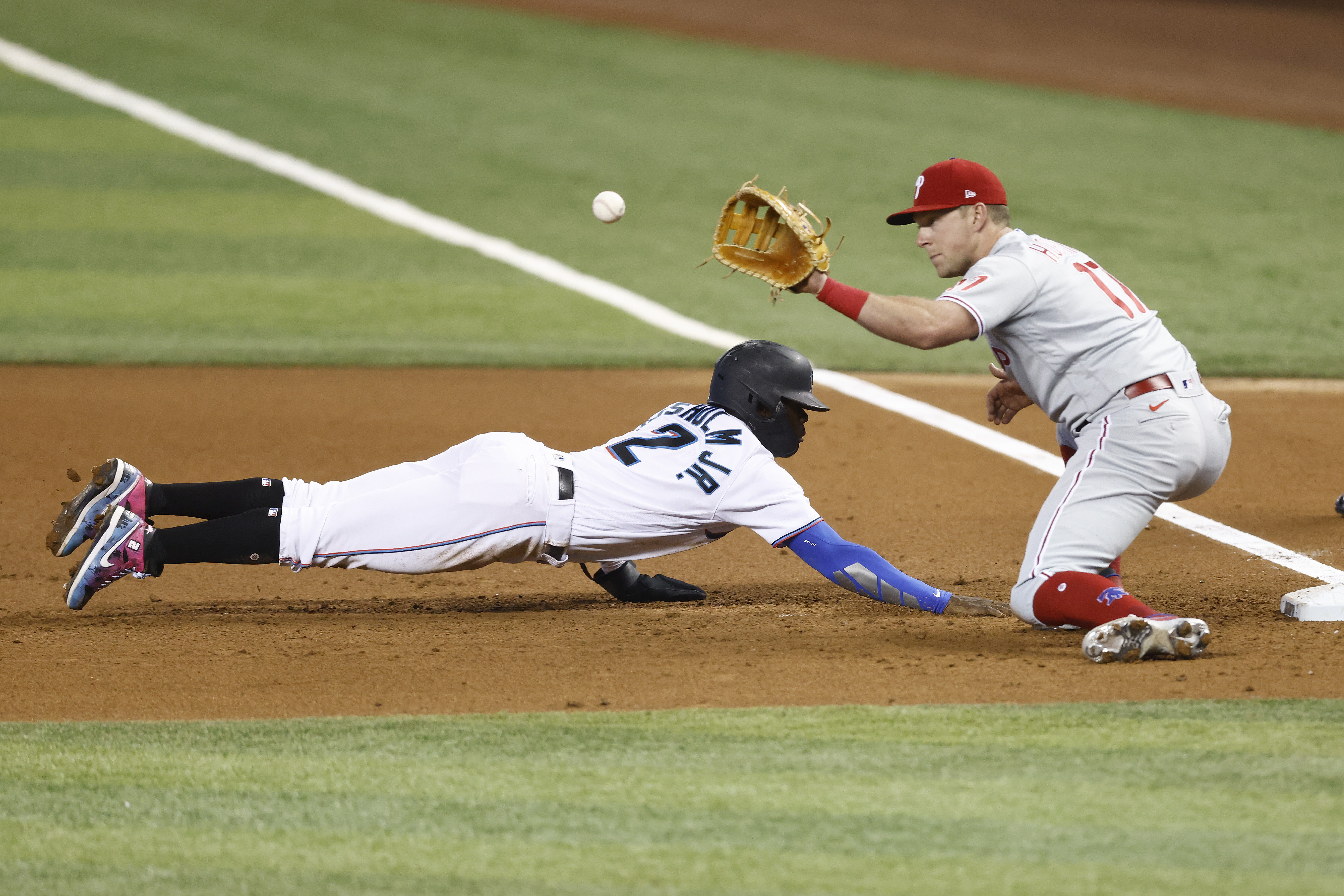 Rhys Hoskins #17 of the Philadelphia Phillies catches a pick-off throw as Jazz Chisholm Jr. #2 of the Miami Marlins slides back during the first inning at loanDepot park
