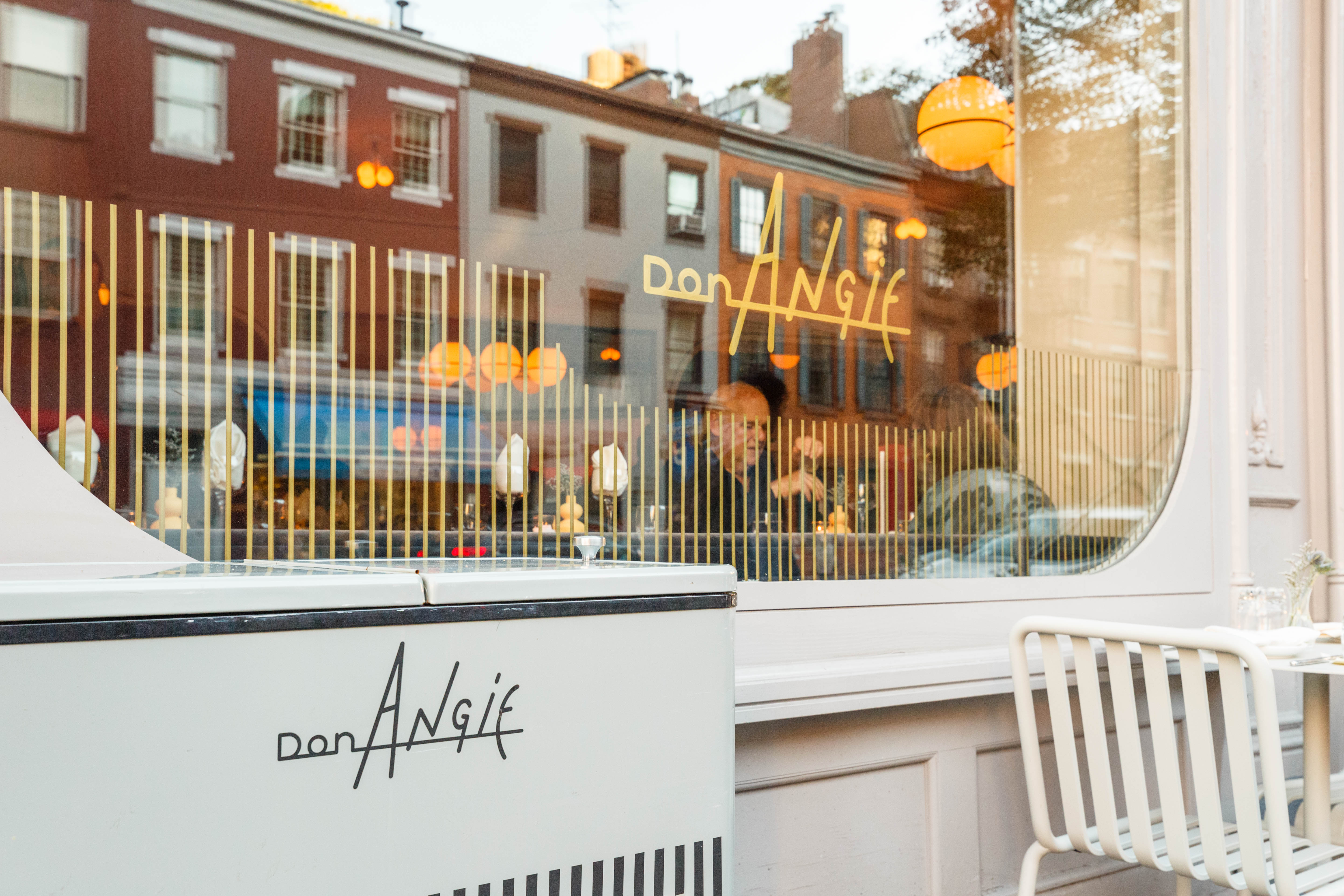 A window with the Don Angie logo on the exterior of the West Village restaurant.