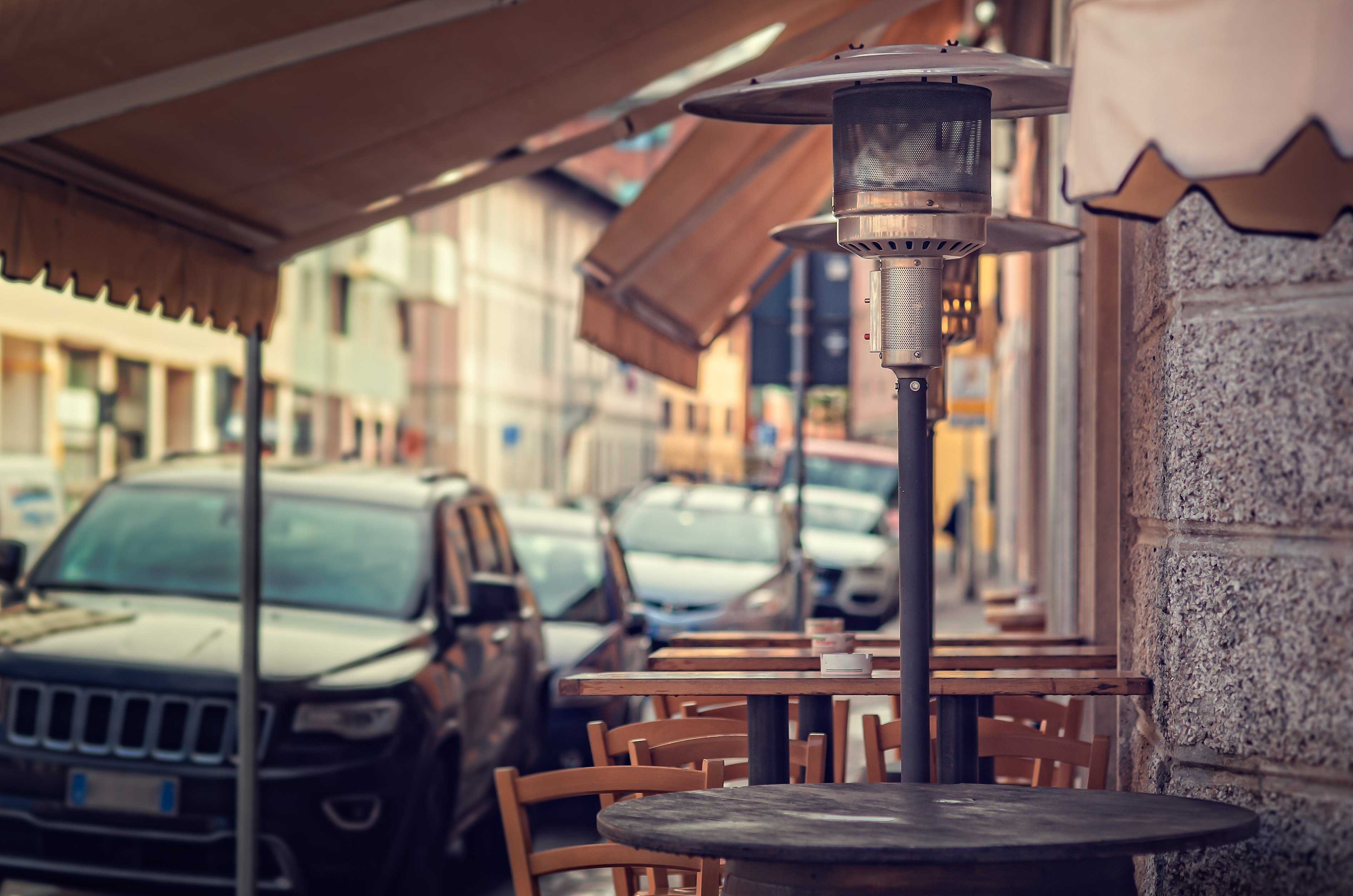 An unlit propane heater standing outside on a street sidewalk with restaurant tables and chairs in the background