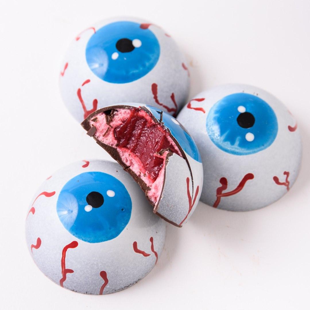 four chocolatey eyeballs, one biten into to show raspberry jelly