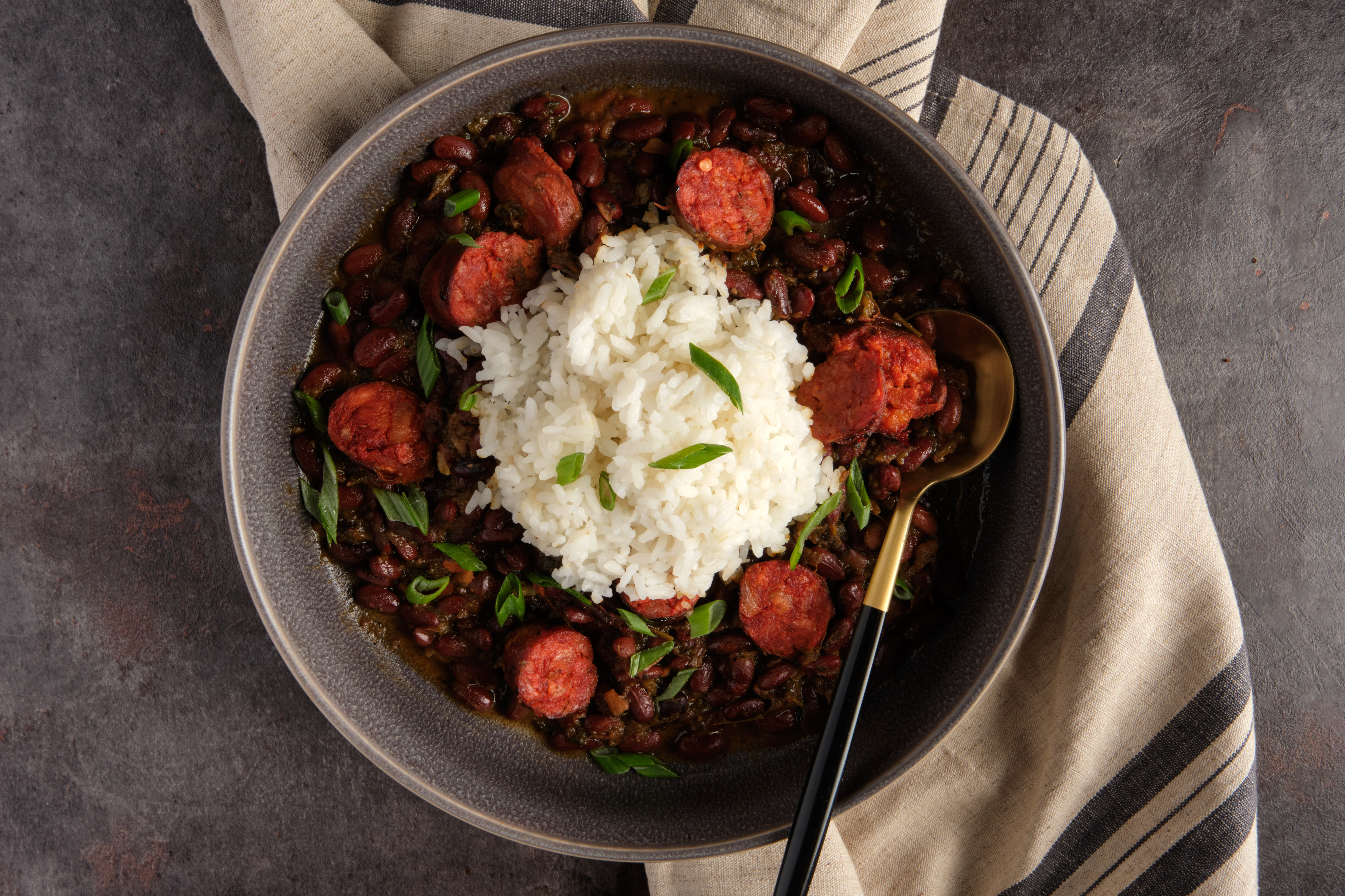 A bowl of red beans and rice sits atop a striped dish towel on a table.