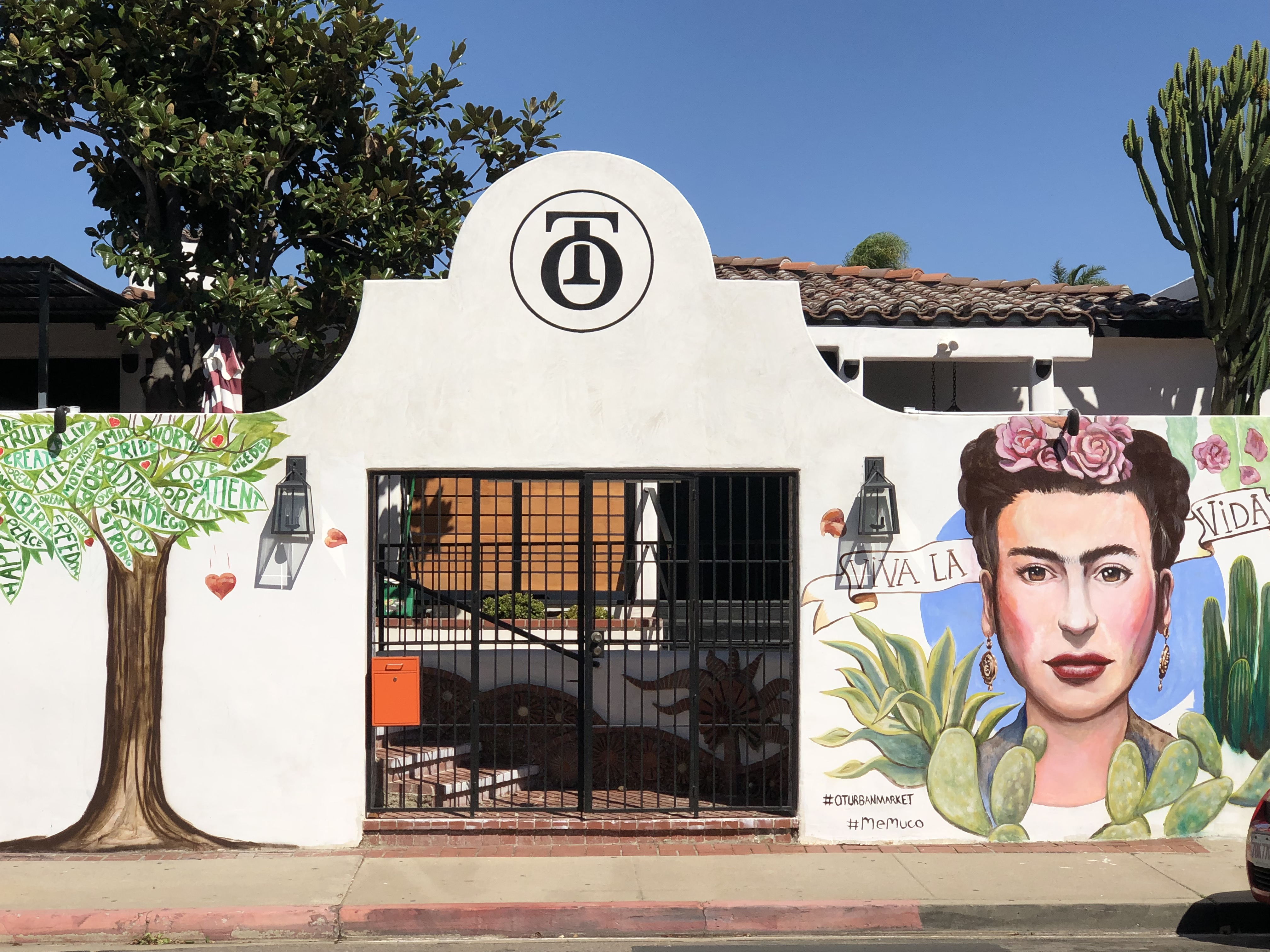 Iron gate and white wall with mural of a tree and portrait of Frieda Kahlo.