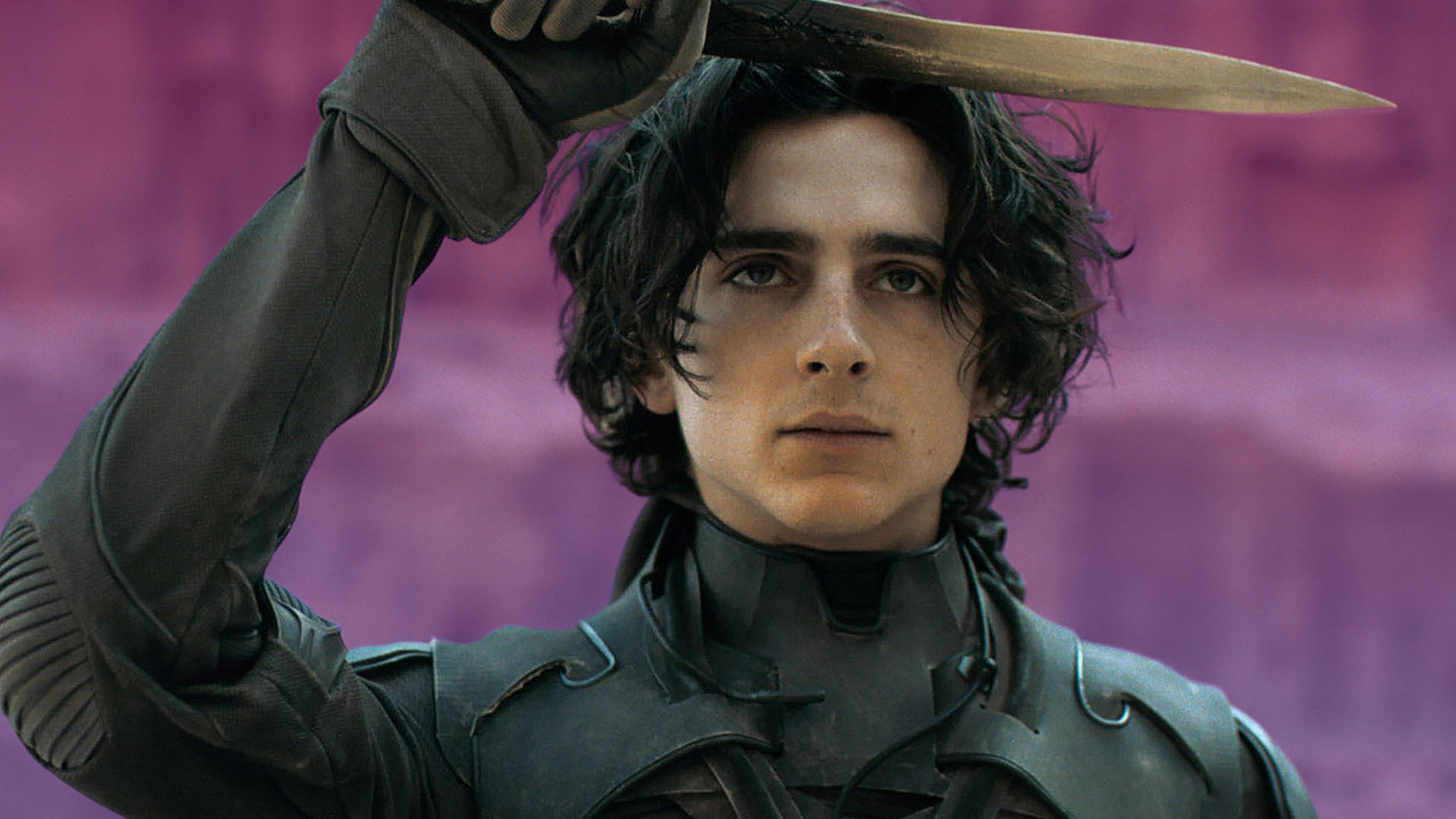 Timothée Chalamet as Paul Atreides in the movie Dune holds a knife to his forehead
