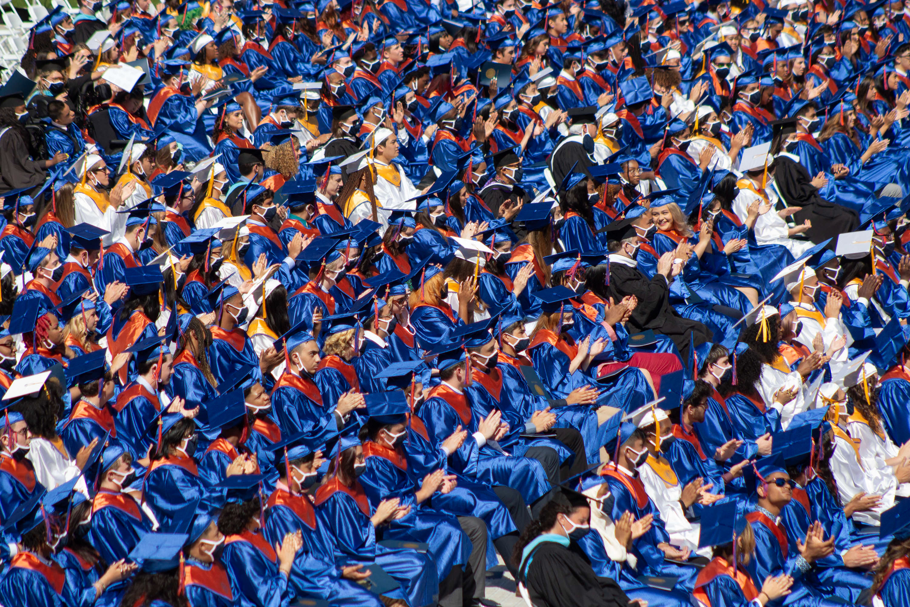 Rows of upcoming graduates applaud during a speech, creating a sea of blue and orange due to the shimmering of their caps and gowns from the sunlight.