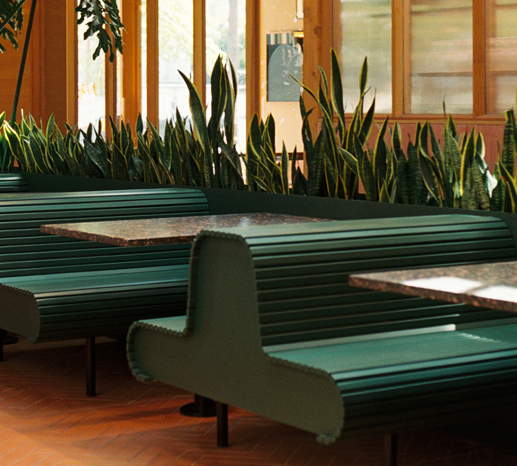 A low angled shot of dark green booths and red tile in a wood-lined restaurant space with lots of greenery.
