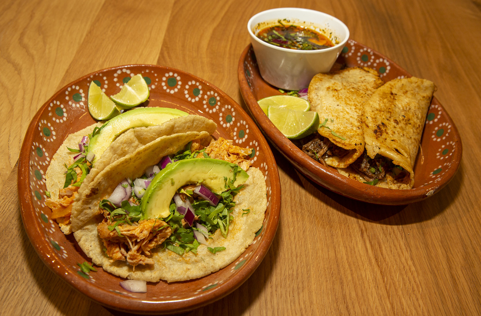 A plate of two tacos topped with avocado, next to a plate of quesabirria.