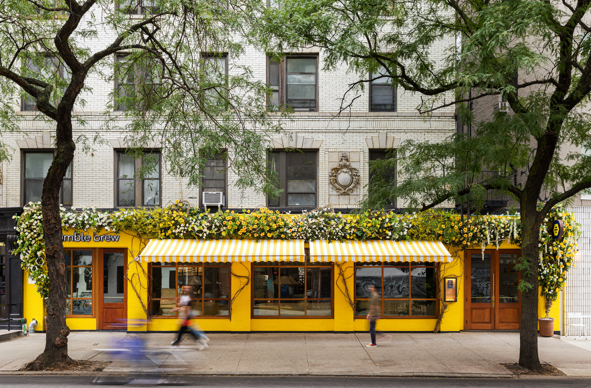 A sidewalk view of a restaurant with a yellow facade.