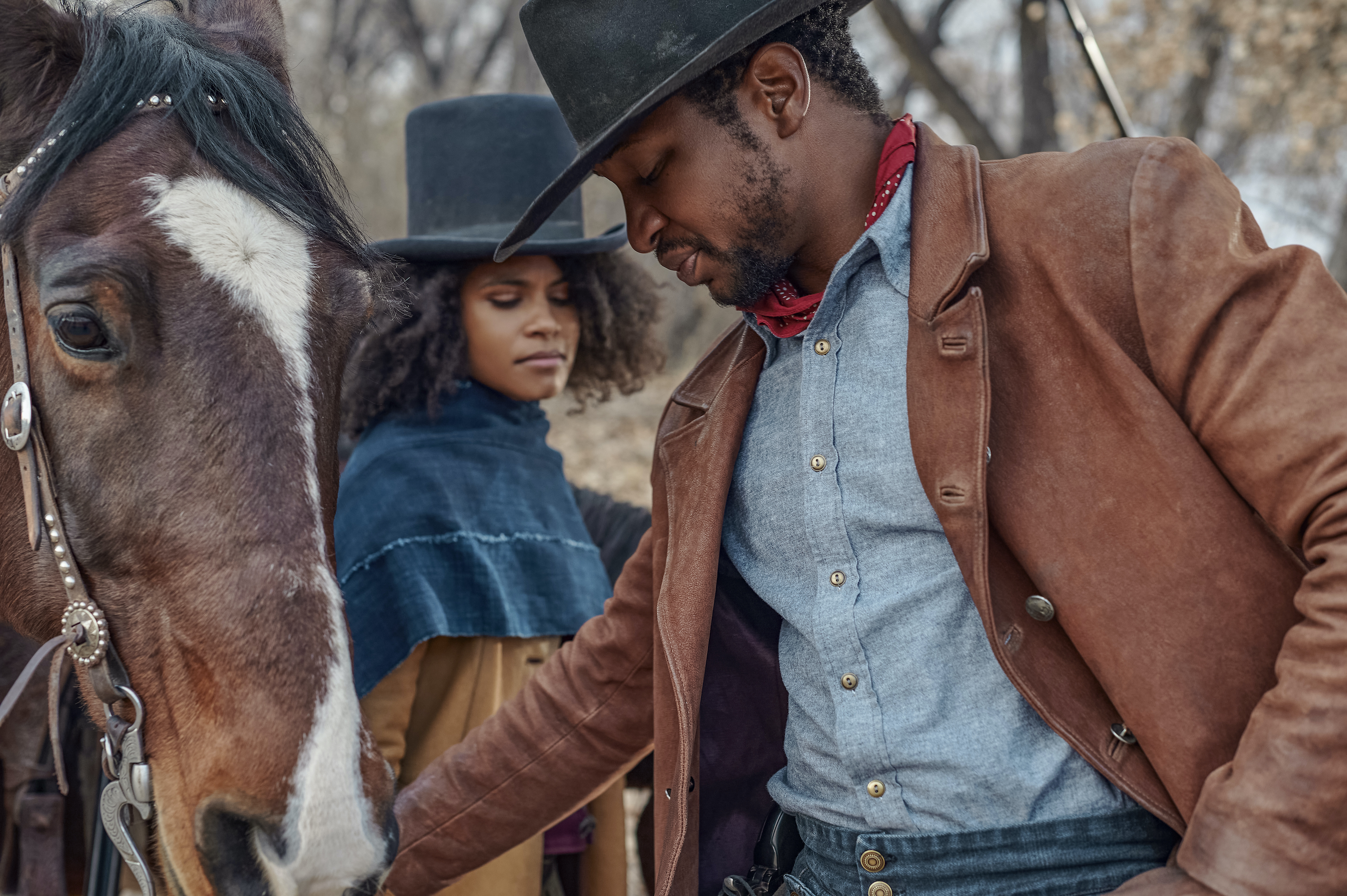 Zazie Beetz and Jonathan Majors wear cowboy hats and stand by a horse, pointedly not looking at each other, in The Harder The Fall