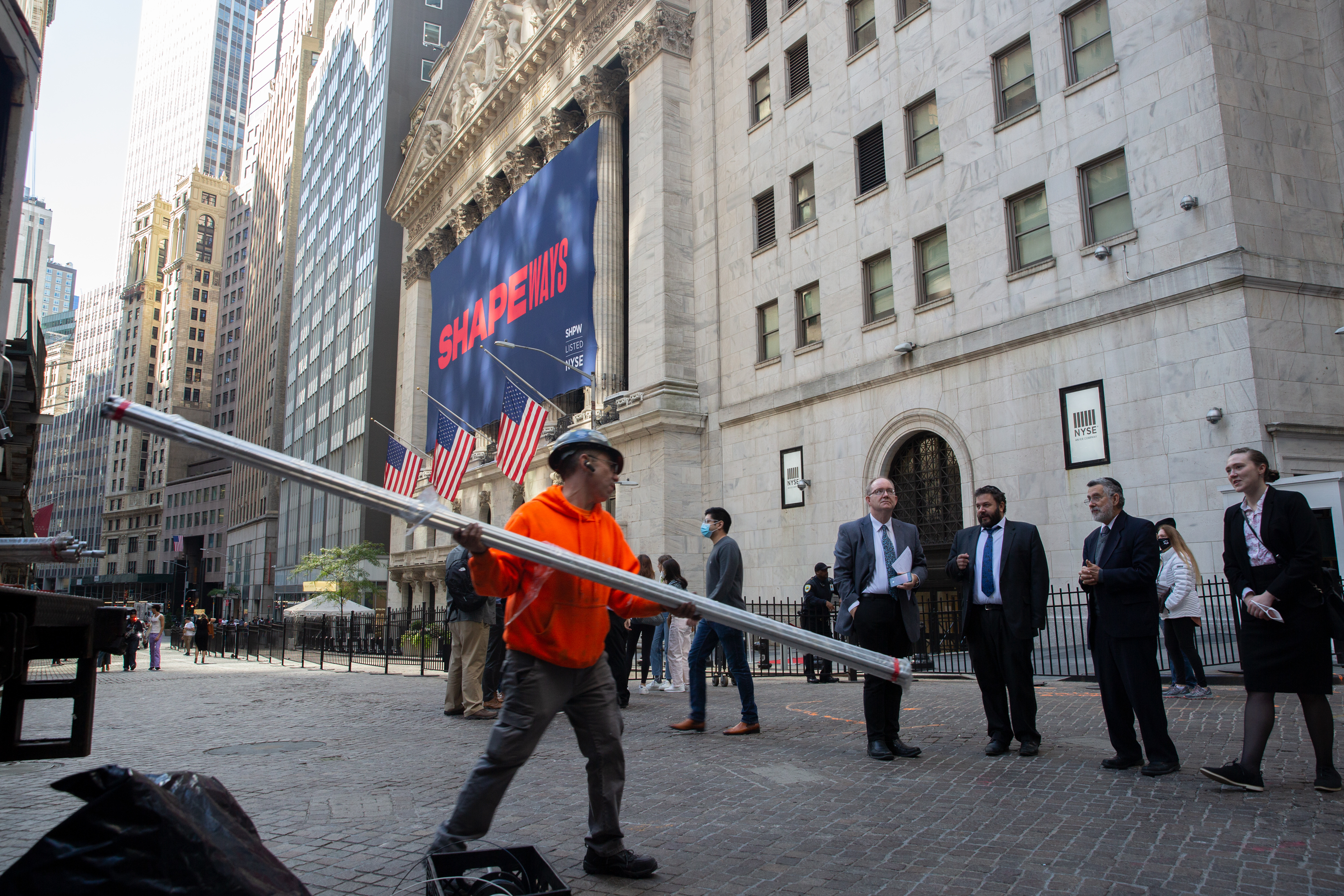 A construction worker transports scaffolding for a project on Wall Street, Oct. 20, 2021.
