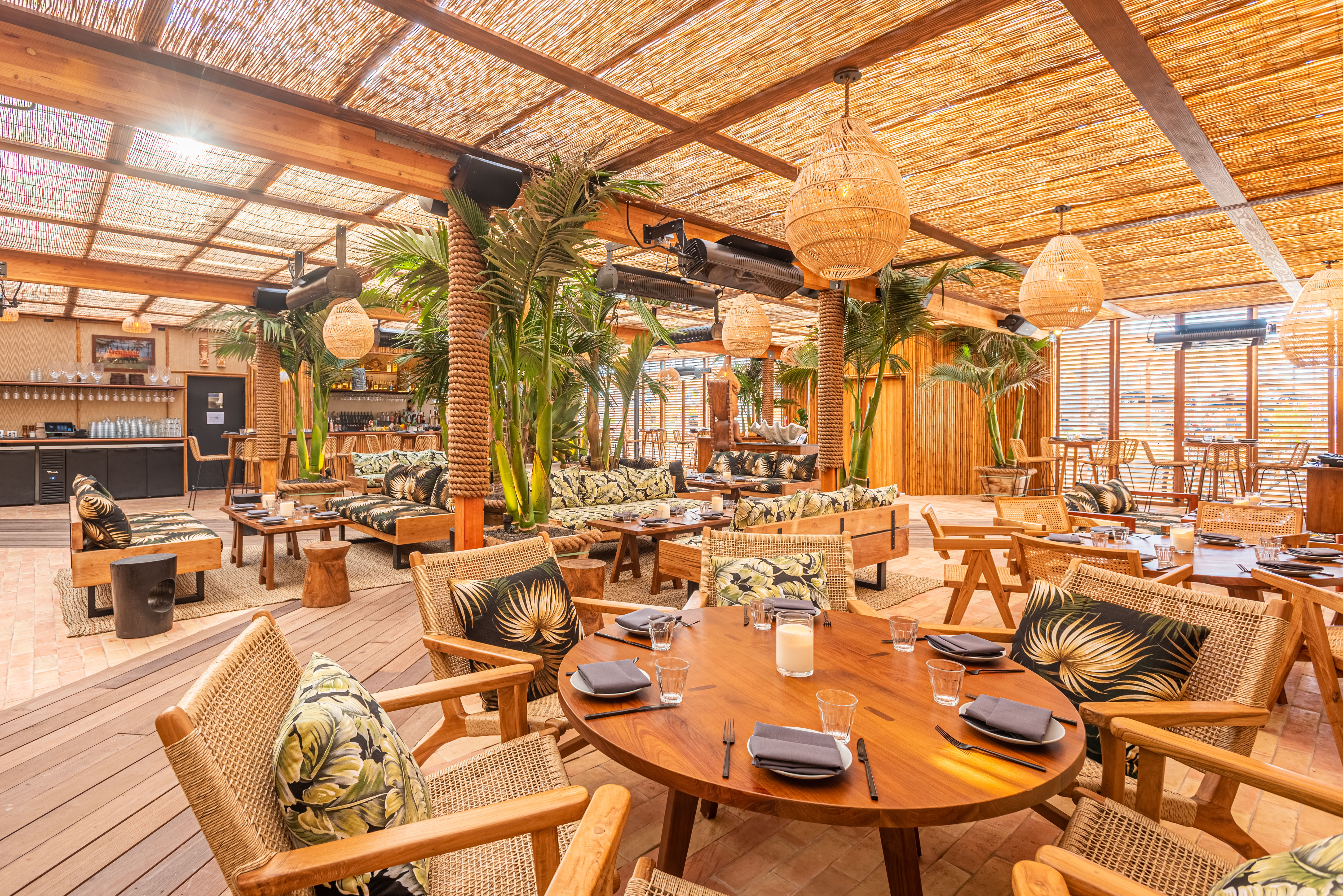 Sunny dining room with Tiki decor, low-level tables and chair, with plants.