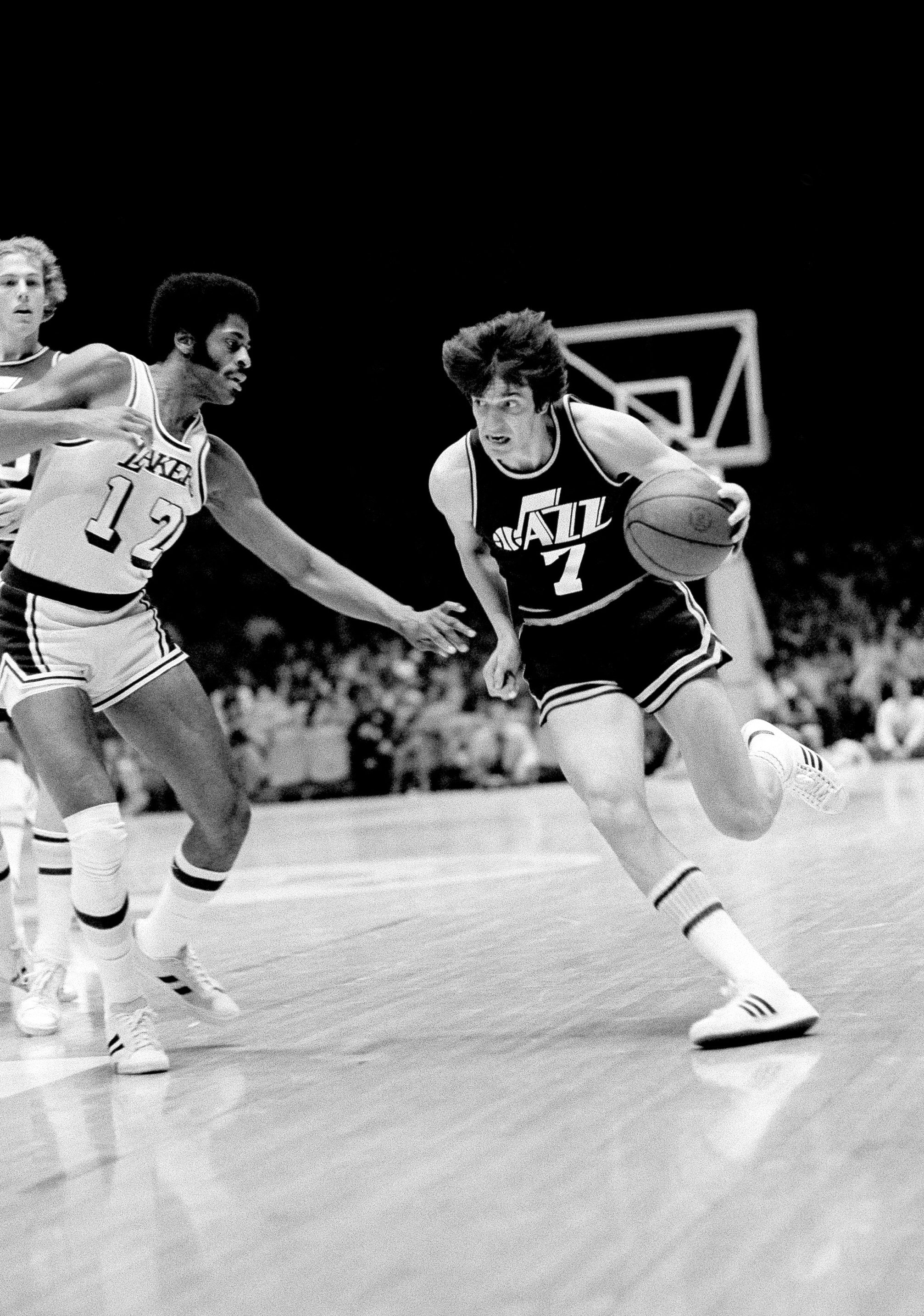 Pete Maravich (7) shows determination by the expression on his face as he drives past Los Angeles Laker Don Chaney