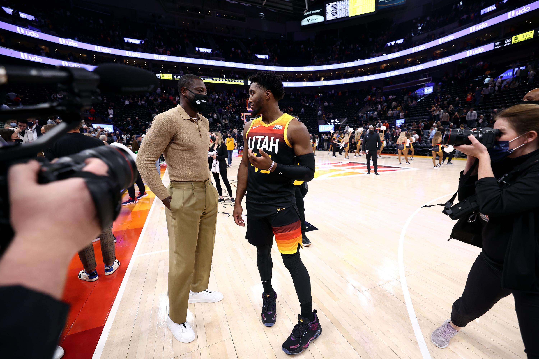 Utah Jazz part owner Dwyane Wade, wearing a suit, talks with Utah Jazz guard Donovan Mitchell