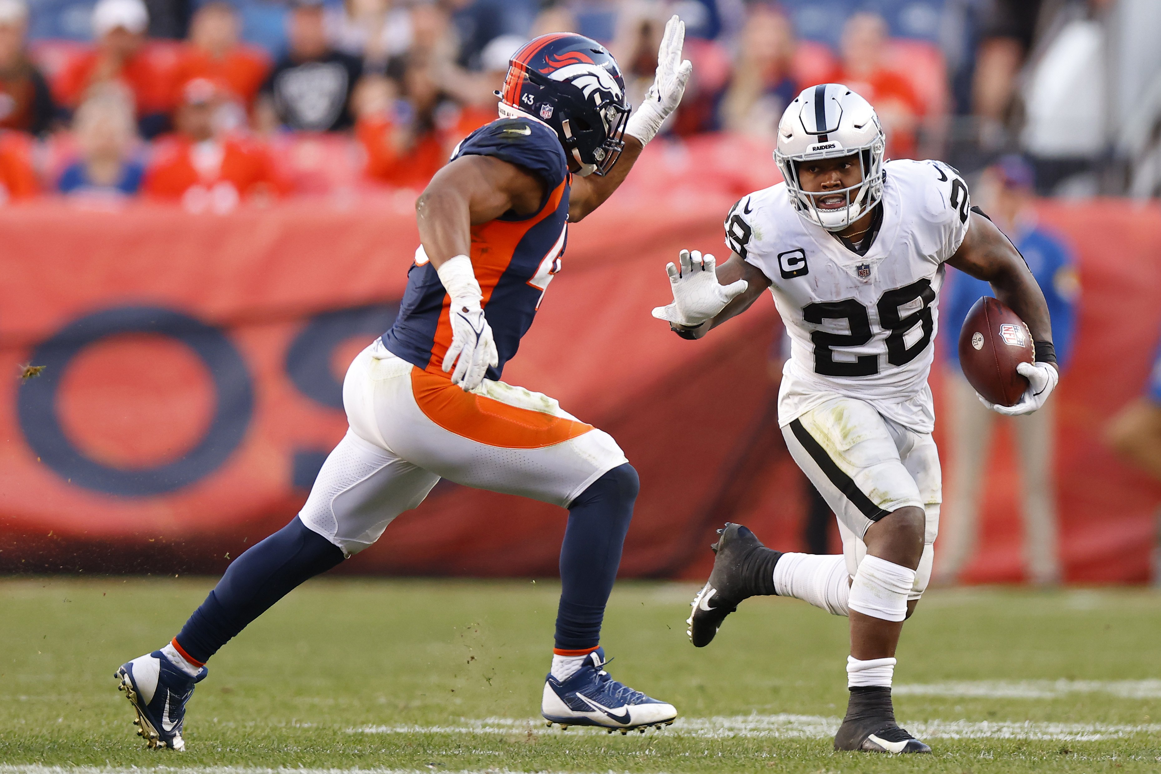 Josh Jacobs #28 of the Las Vegas Raiders runs with the ball against Micah Kiser #43 of the Denver Broncos during the fourth quarter at Empower Field At Mile High on October 17, 2021 in Denver, Colorado.