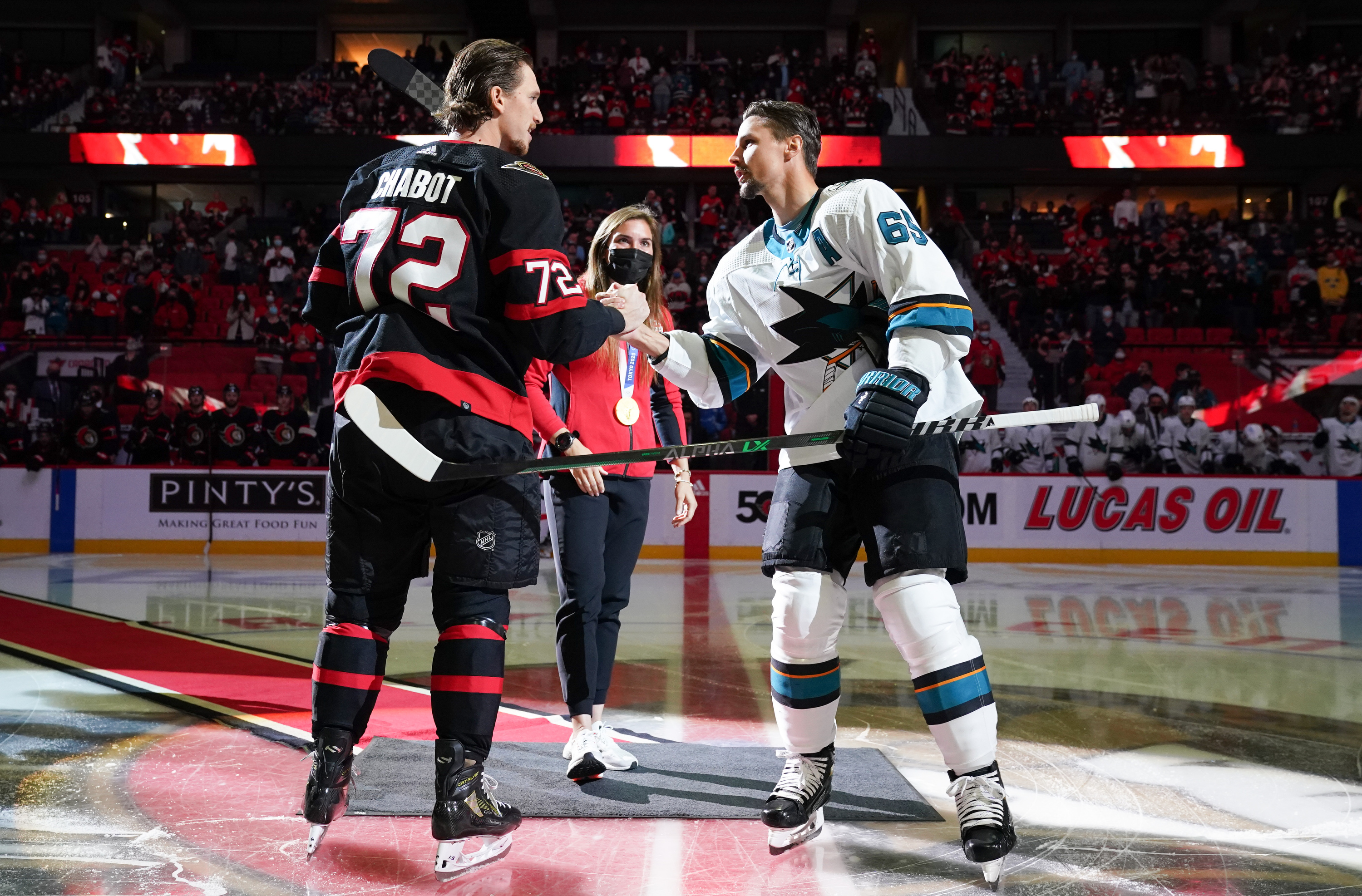 Thomas Chabot #72 of the Ottawa Senators and Erik Karlsson #65 of the San Jose Sharks shake hands after a ceremonial face-off at Canadian Tire Centre on October 21, 2021 in Ottawa, Ontario, Canada.