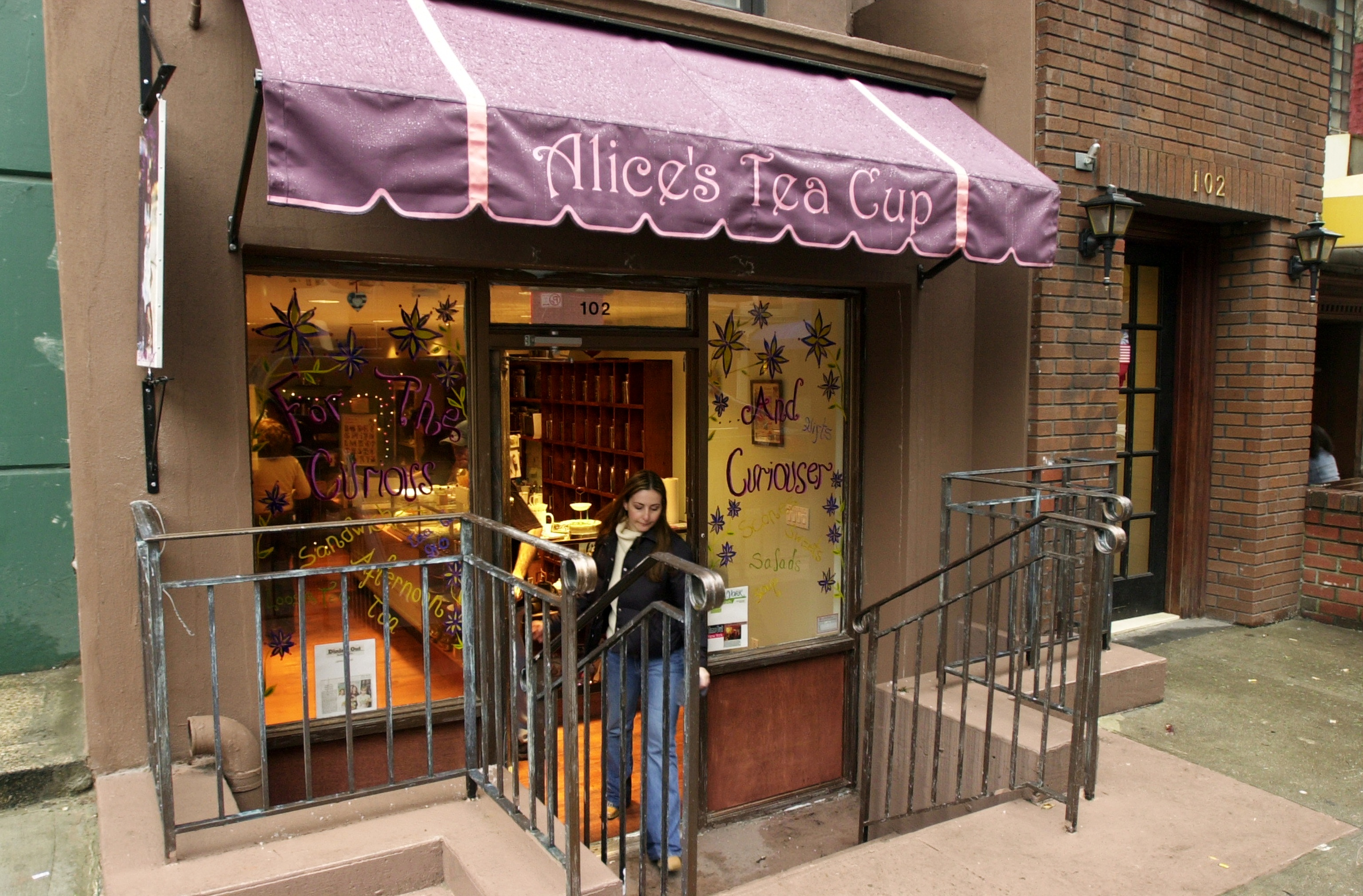 A person exits the front door of the original Upper West Side location of Alice's Tea Cup in Manhattan.