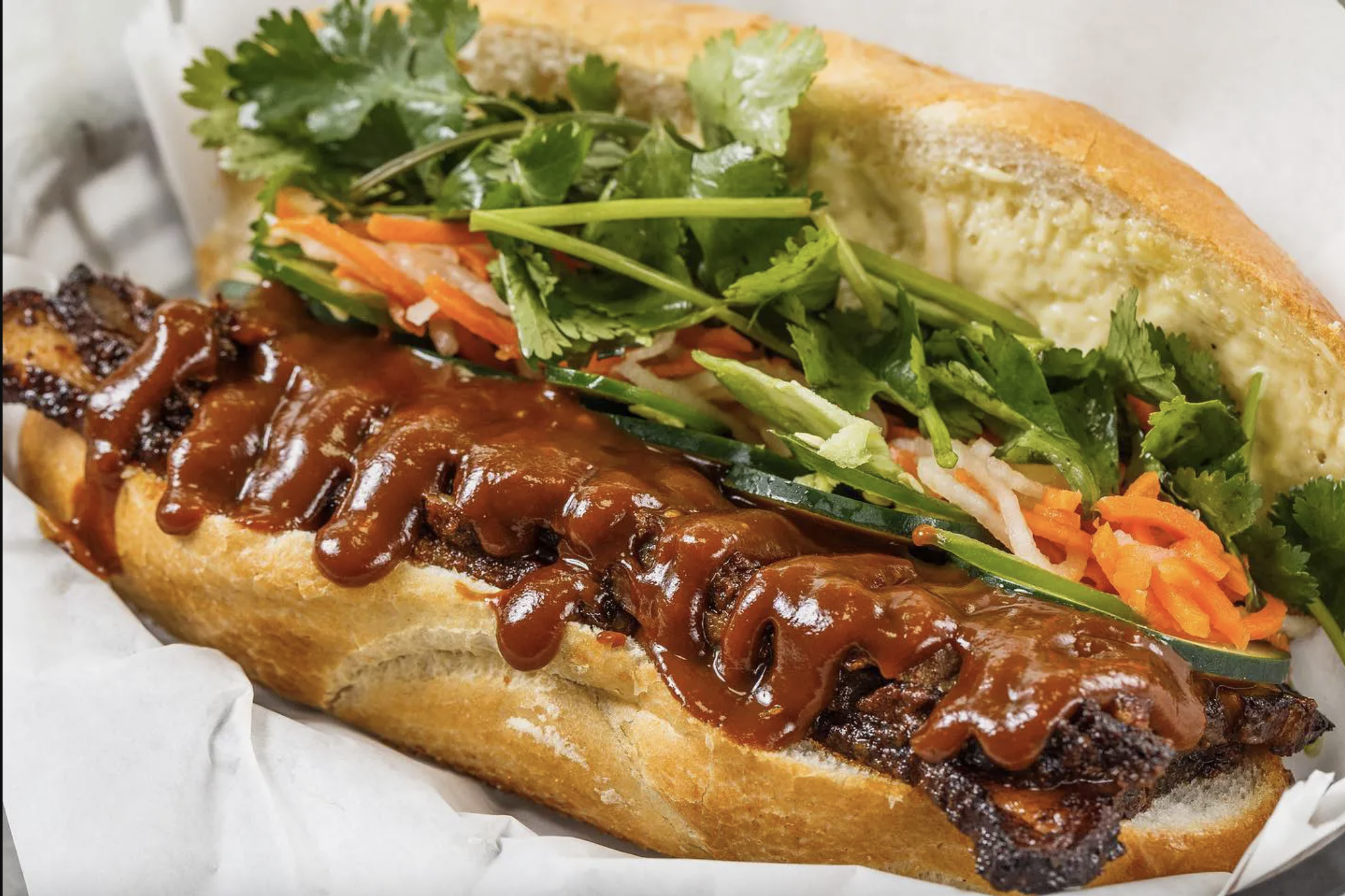 A baguette with saucy brisket comes topped with carrots, cucumbers, radish, and cilantro at Banh Mi Boys.