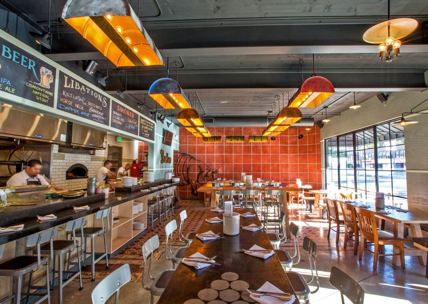 A wide look at an orange, wood-lined restaurant space with high top seats and open kitchen.