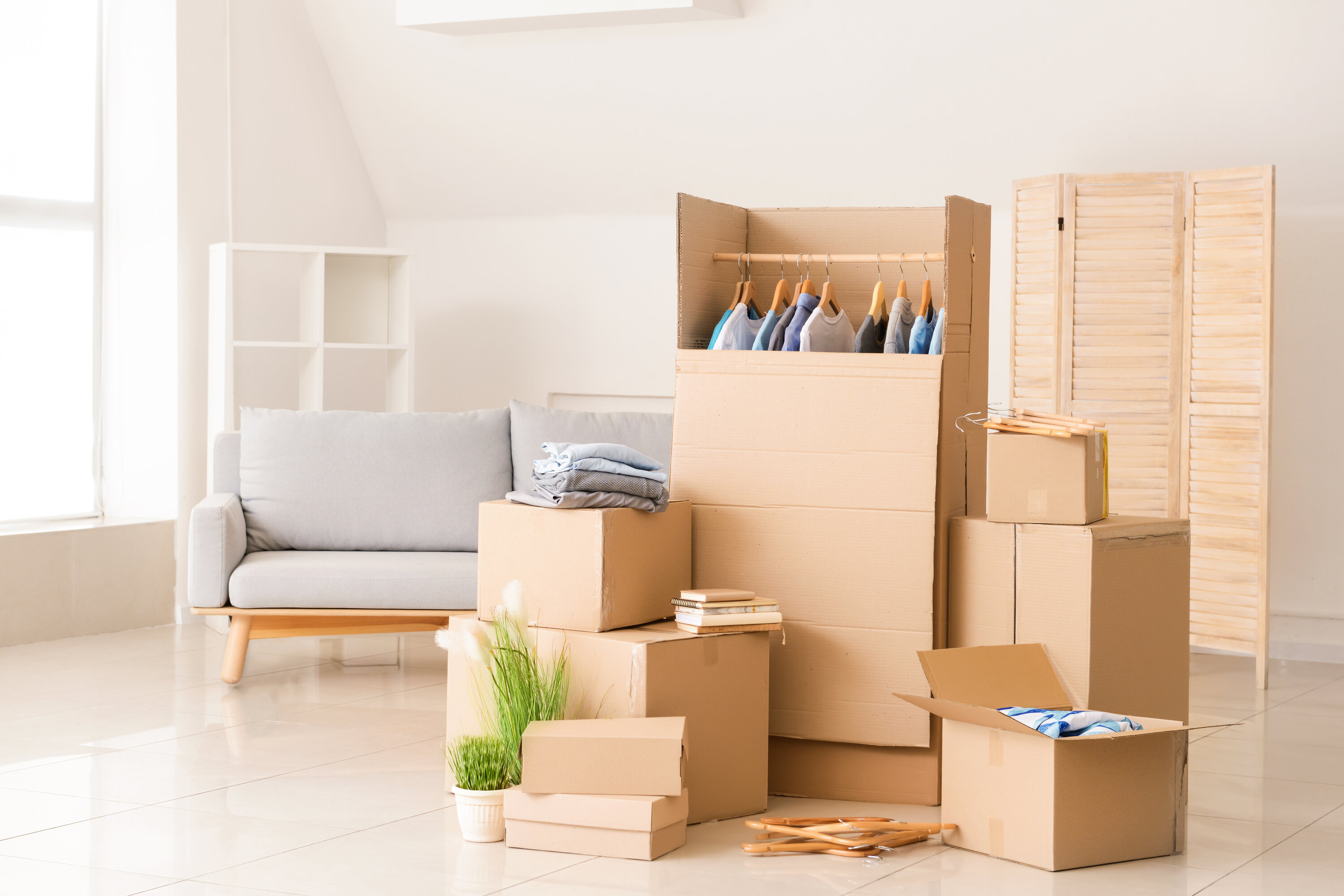 Multiple cardboard boxes stacked in multiple stacks filled with items to move, they are in a white bed room with window lighting with a small couch and wardrobe in the back