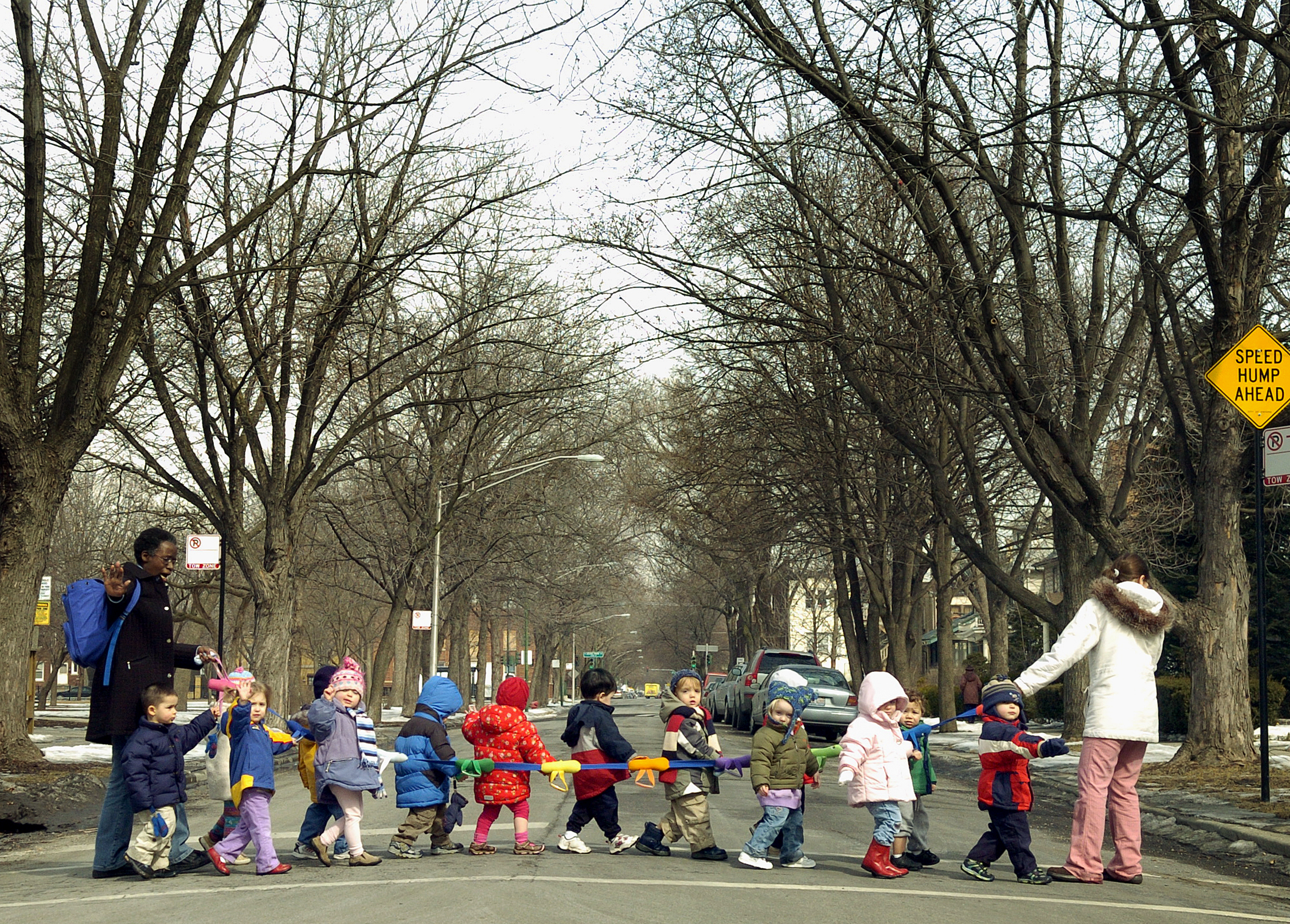 Daycare employees motion for cars to halt while walking a trail of toddlers across a North Side street in 2007.