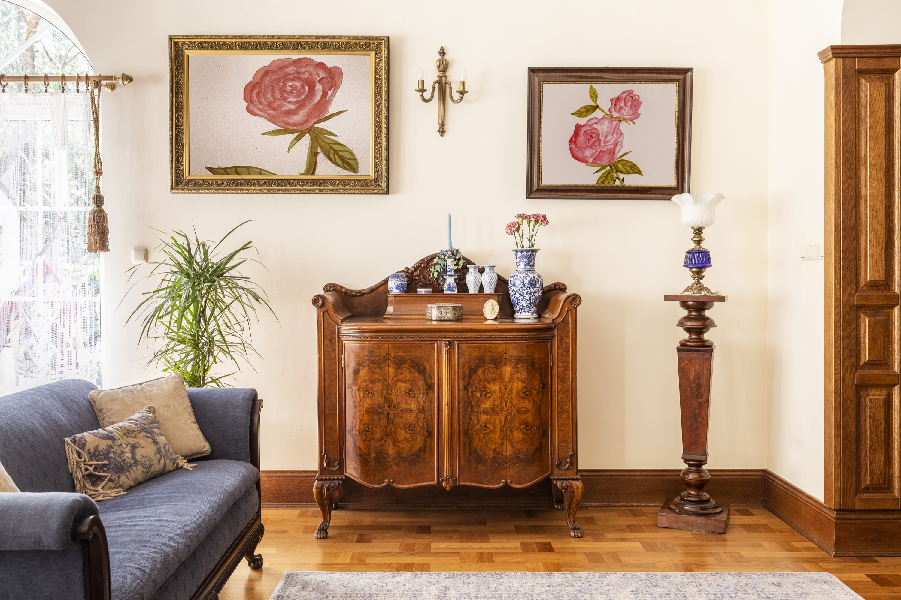 A light filled room with cream walls and wood floors, antique wood dresser in the center, with other antique lamps, blue sofa, vases, and 2 rose paintings hung on the wall where the dresser is