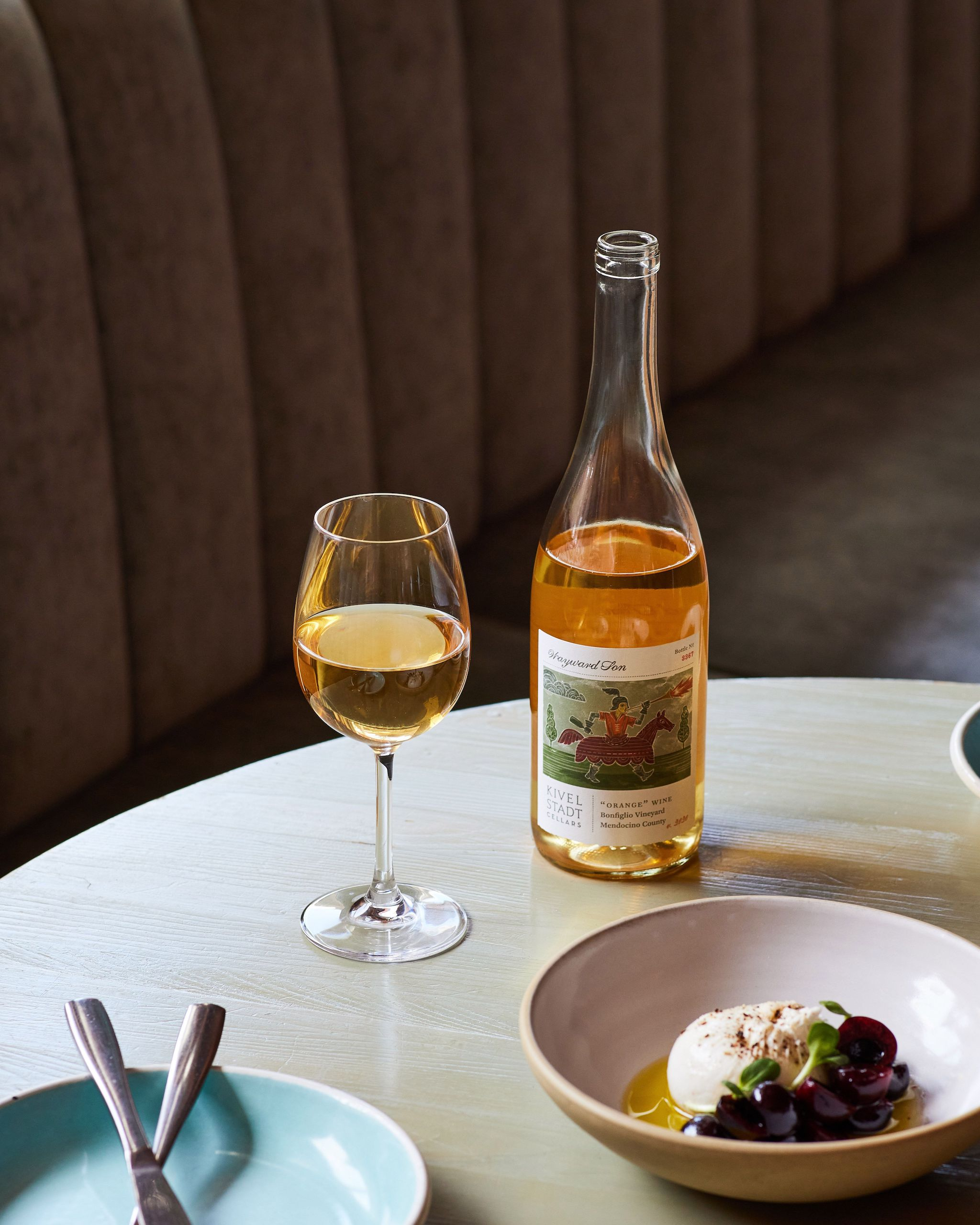 A blonde wood table with a bottle of rosé wine and glass with a bowl of cheese and a blue plate.