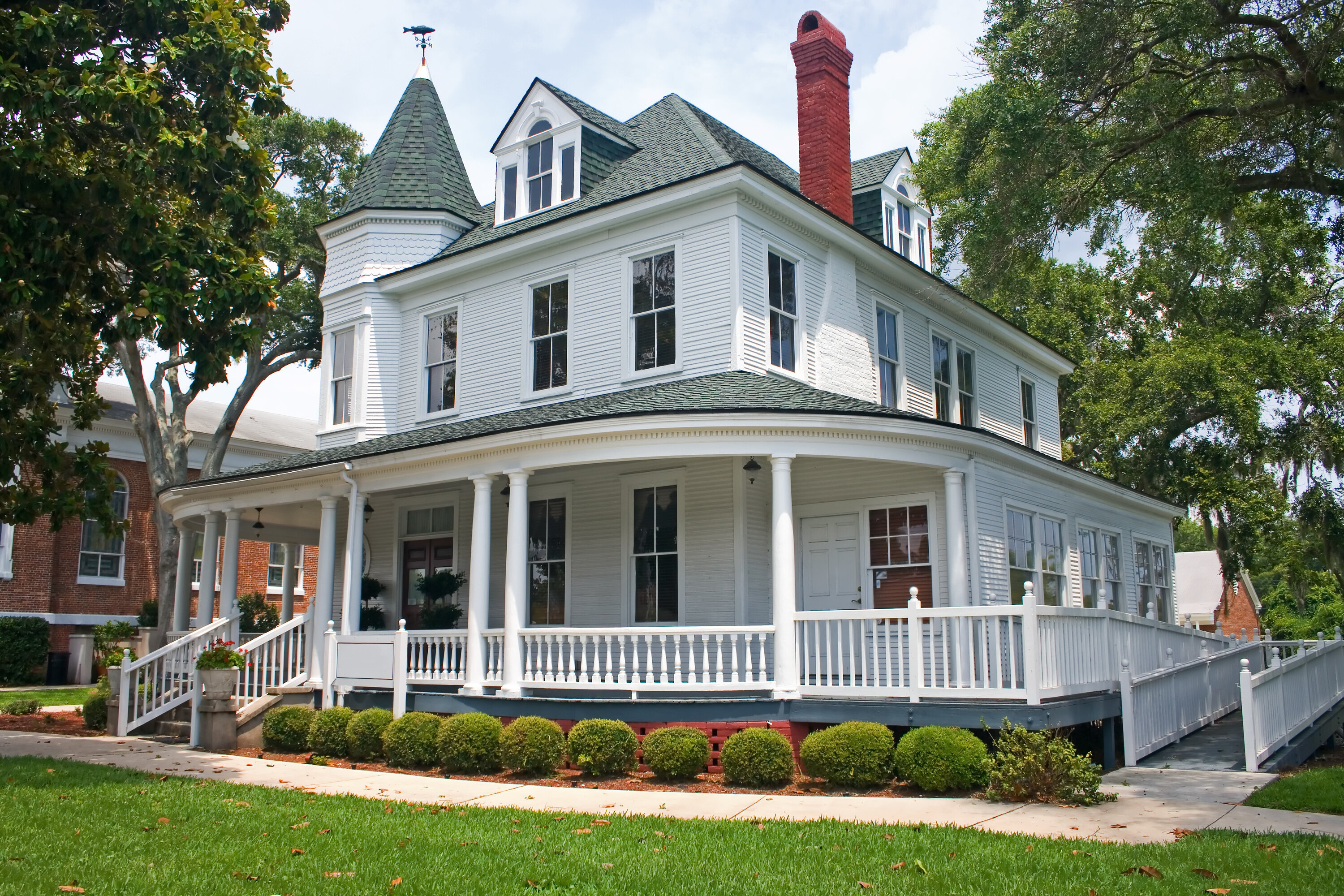 A 2 story white victorian southern home with a wrap around front porch, American flag, red chimney, and a grass front Lon with a sidewalk and bushes
